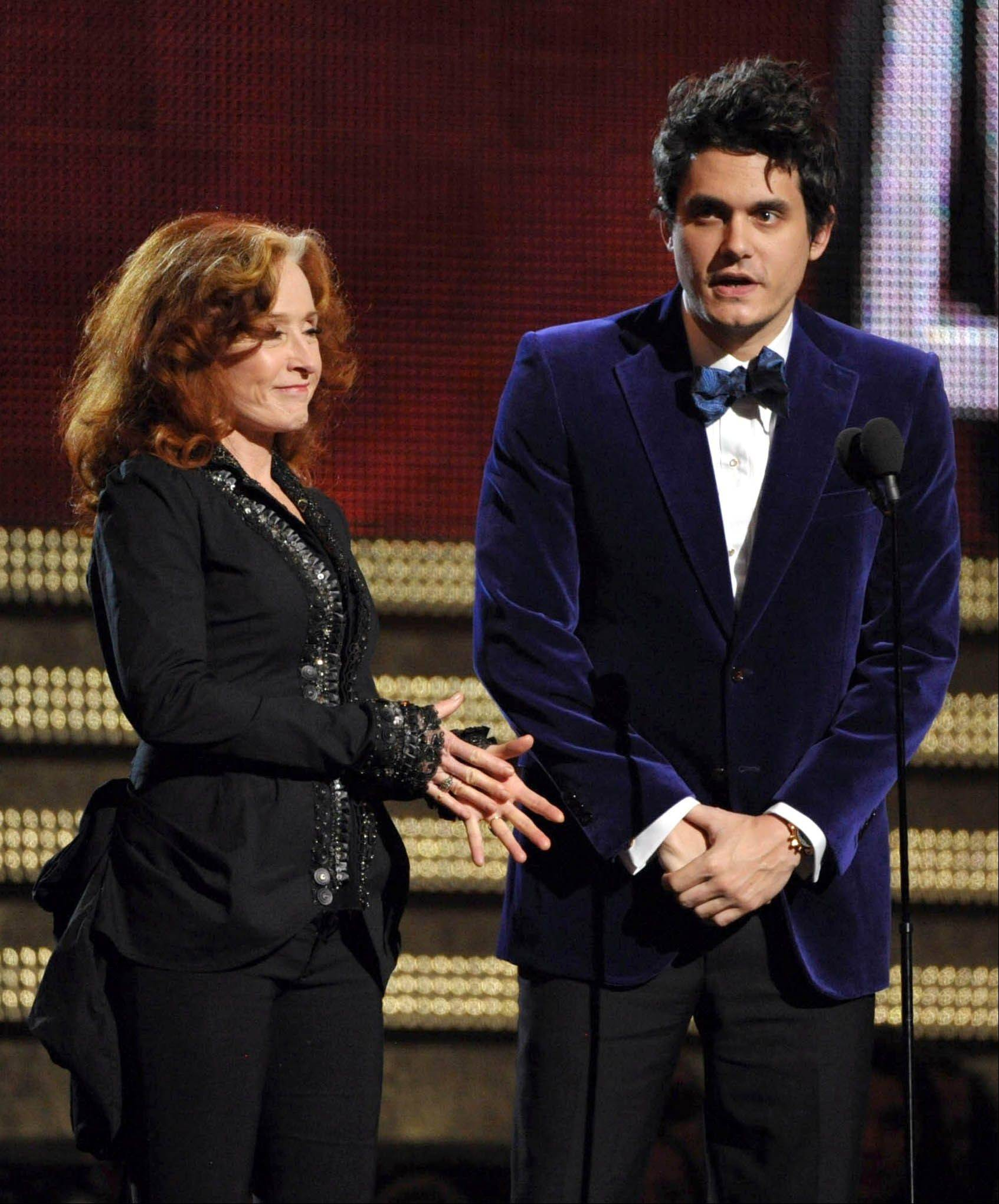 Musicians Bonnie Raitt and John Mayer present at the 55th annual Grammy Awards on Sunday, Feb. 10, 2013, in Los Angeles.