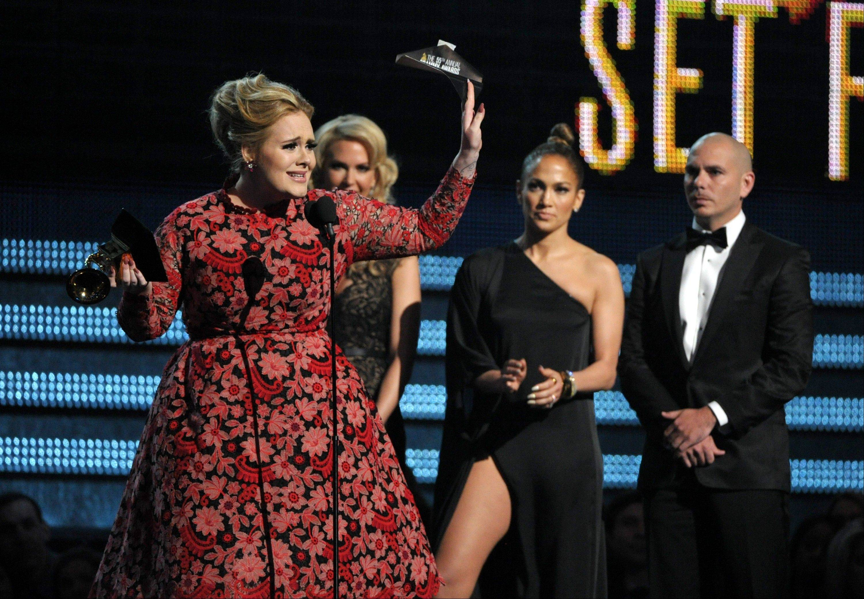 "Adele accepts the award for best pop solo performance for ""Set Fire to the Rain"" at the 55th annual Grammy Awards on Sunday, Feb. 10, 2013, in Los Angeles. Looking on from right are presenters Pitbull and Jennifer Lopez."
