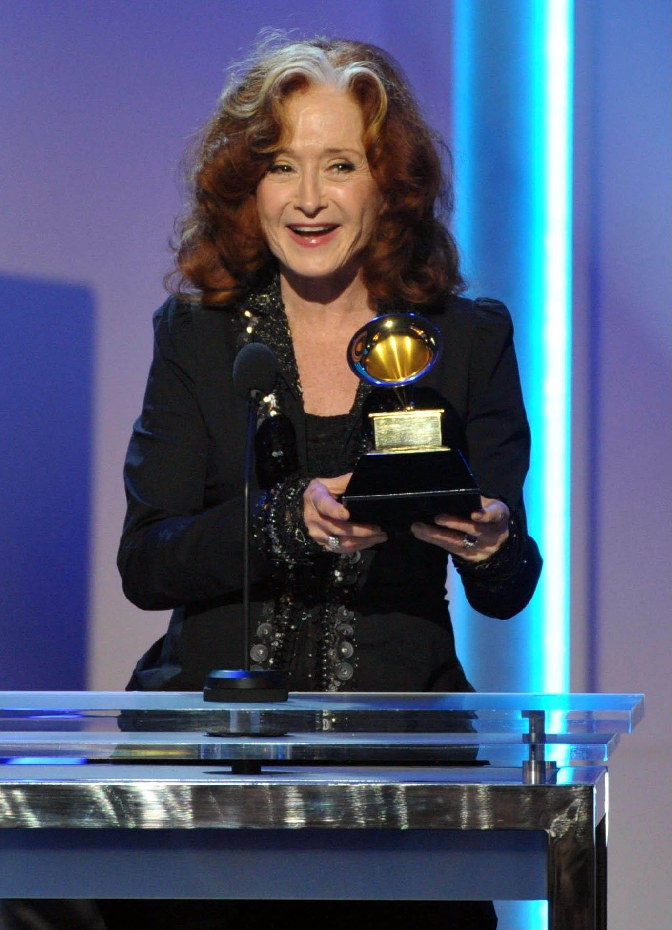 "Bonnie Raitt accepts the award for best Americana album for ""Slipstream"" during the pre-telecast at the 55th annual Grammy Awards on Sunday, Feb. 10, 2013, in Los Angeles. )"