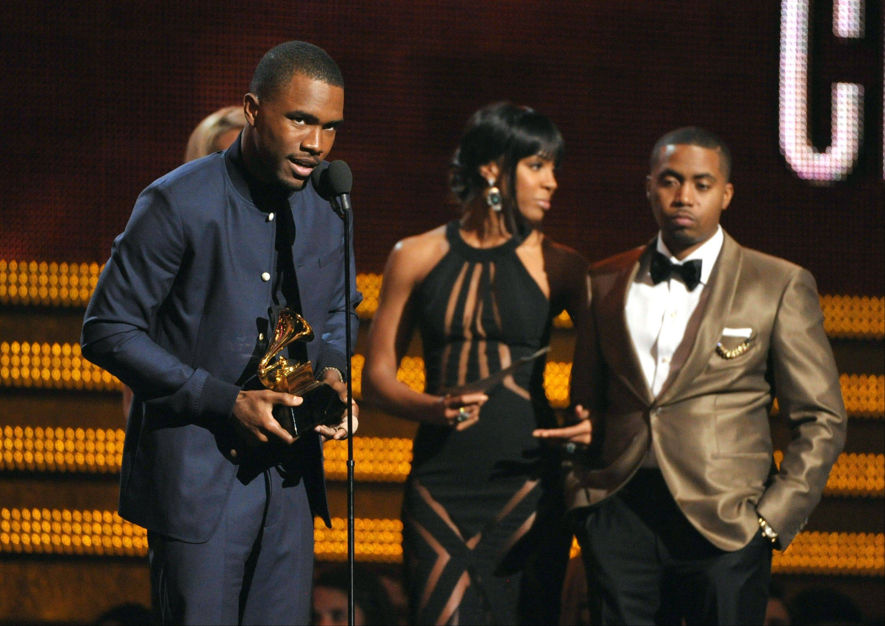 Frank Ocean accepts the award for best urban contemporary album at the 55th annual Grammy Awards on Sunday, Feb. 10, 2013, in Los Angeles. Looking on from right presenters Kelly Rowland and Nas.