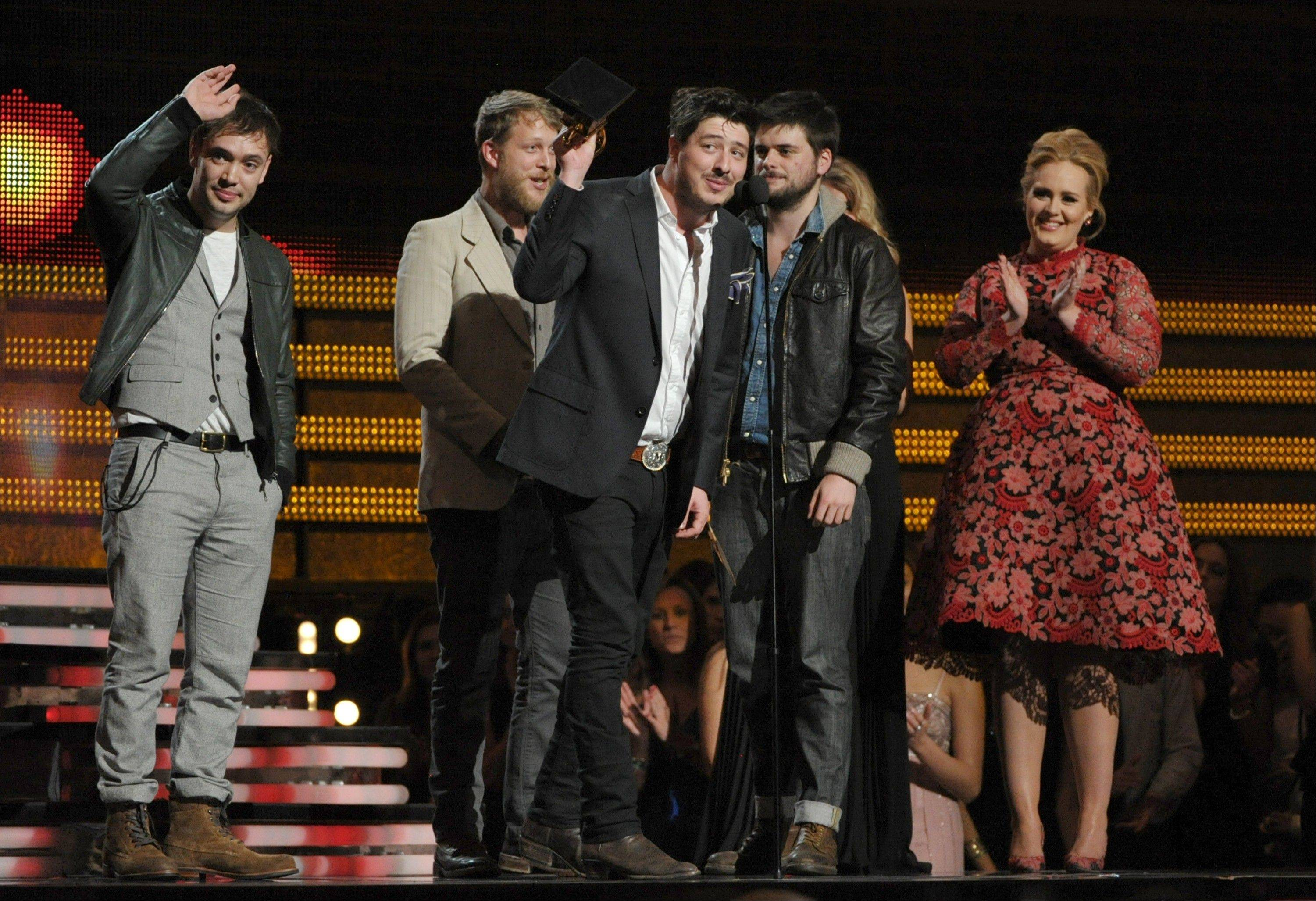 "Mumford & Sons, from left, Ben Lovett, Ted Dwayne, Marcus Mumford and Country Winston Marshall accept the award for album of the year for ""Babel"" at the 55th annual Grammy Awards on Sunday, Feb. 10, 2013, in Los Angeles. Presenter Adele, right, claps."