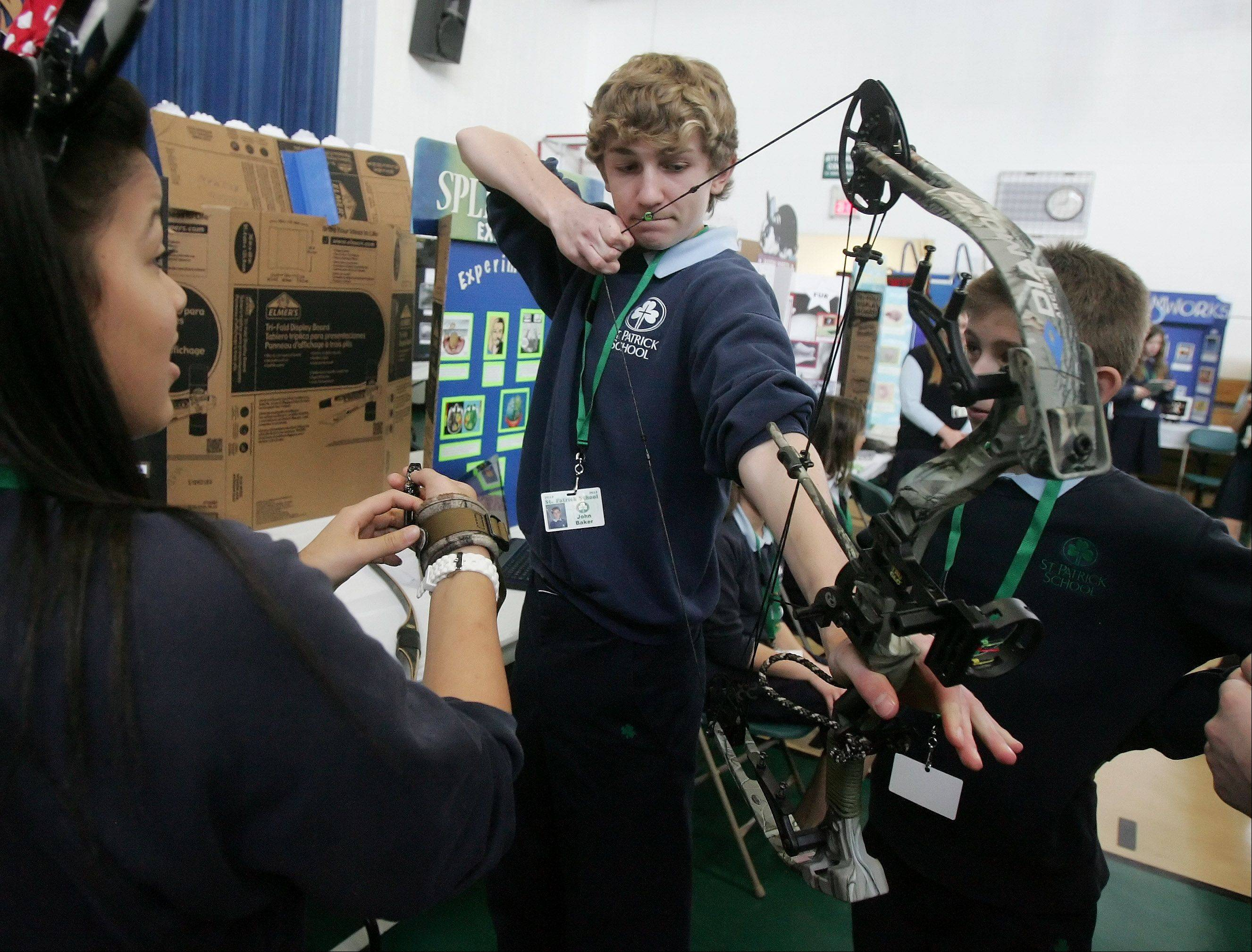 Eighth grader John Baker demonstrates his bow at his exhibit on archery during the Academic Fair Wednesday at St. Patrick Catholic School in Wadsworth.