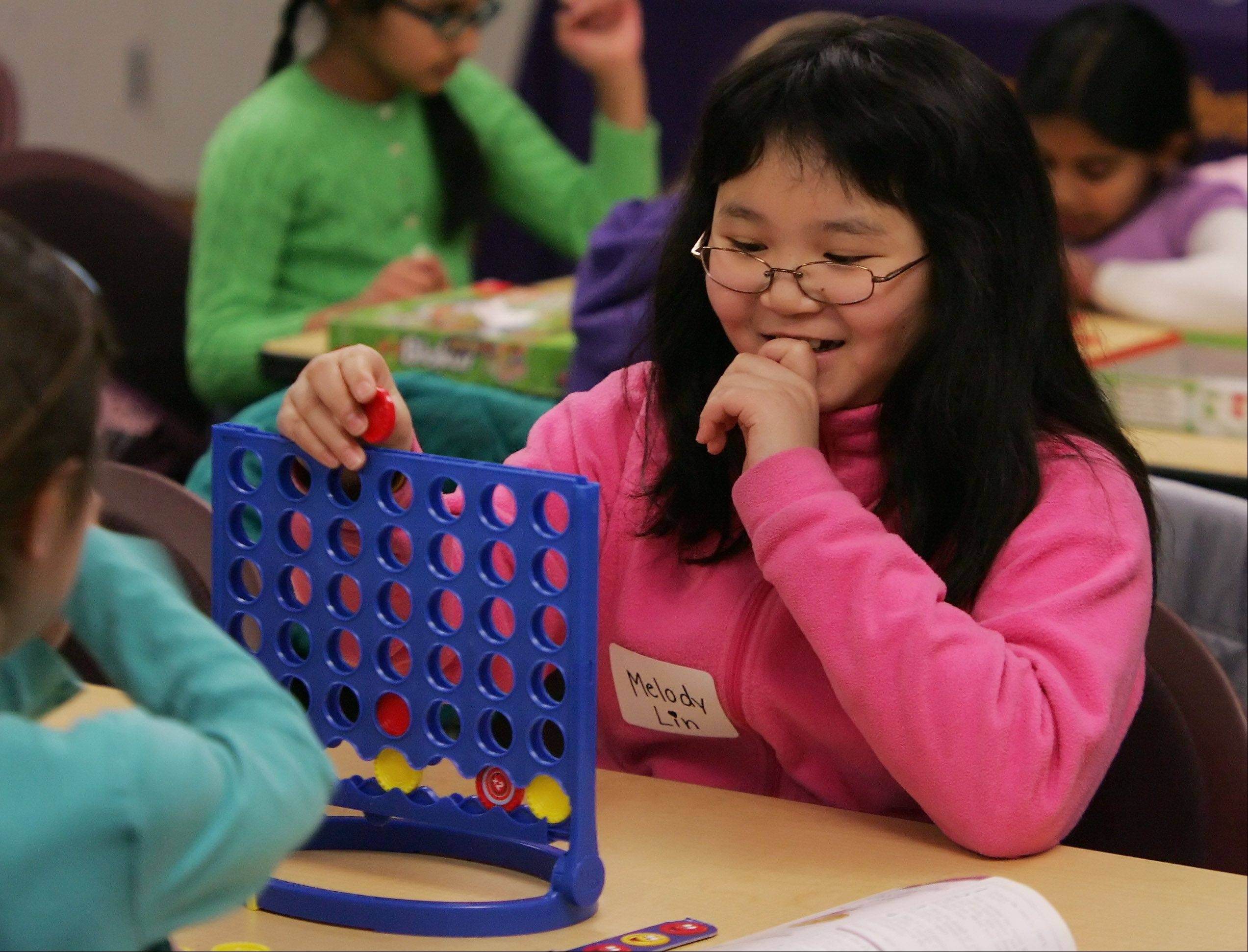 Melody Lin, 9, thinks about her next move in Connect 4 during a snow day Thursday at Vernon Area Public Library in Lincolnshire.