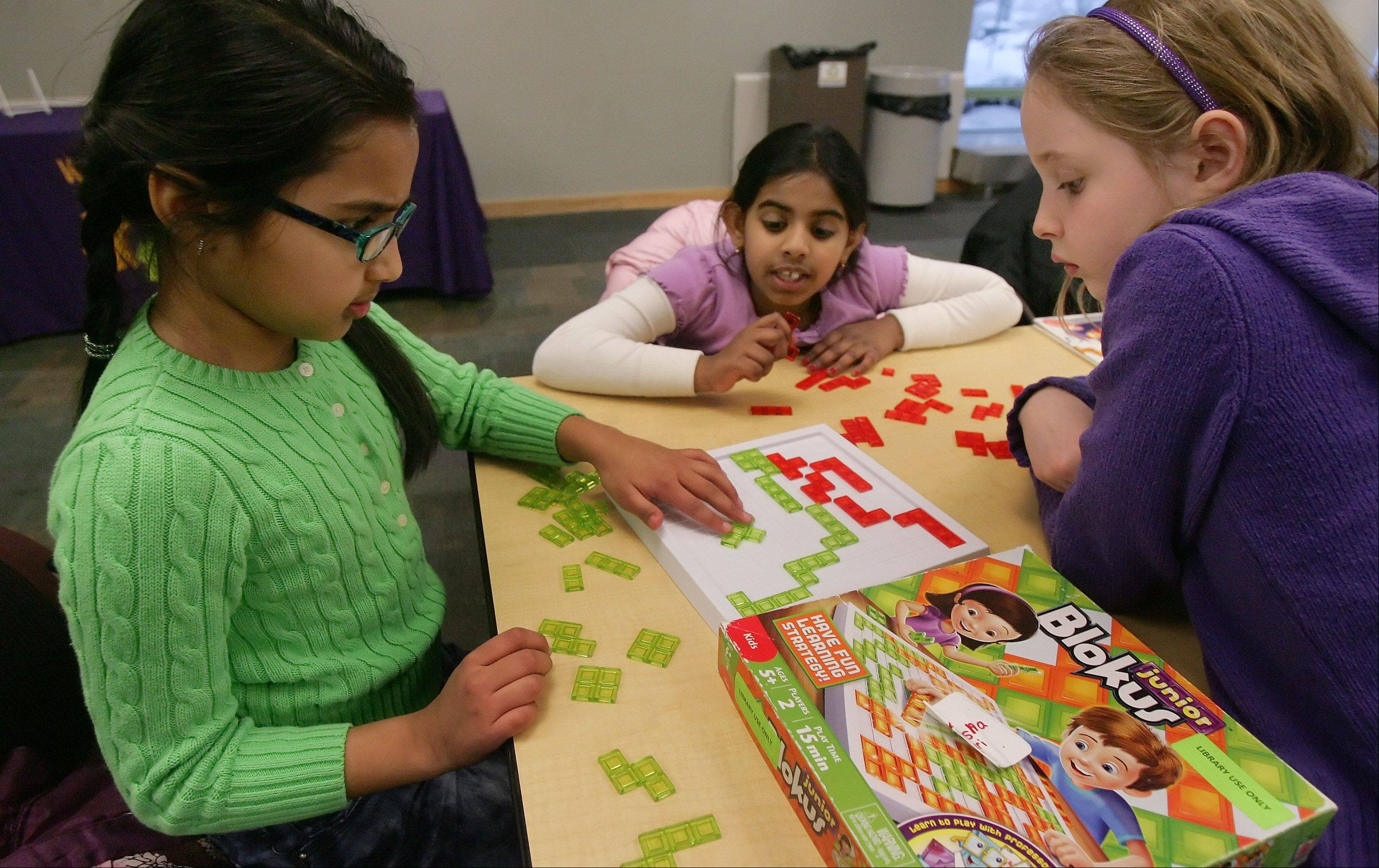 Meha Krishna, 8, left, Sruja Konada, 8, and Emery Etzel, 9, play Blokus during a snow day Thursday at Vernon Area Public Library in Lincolnshire.