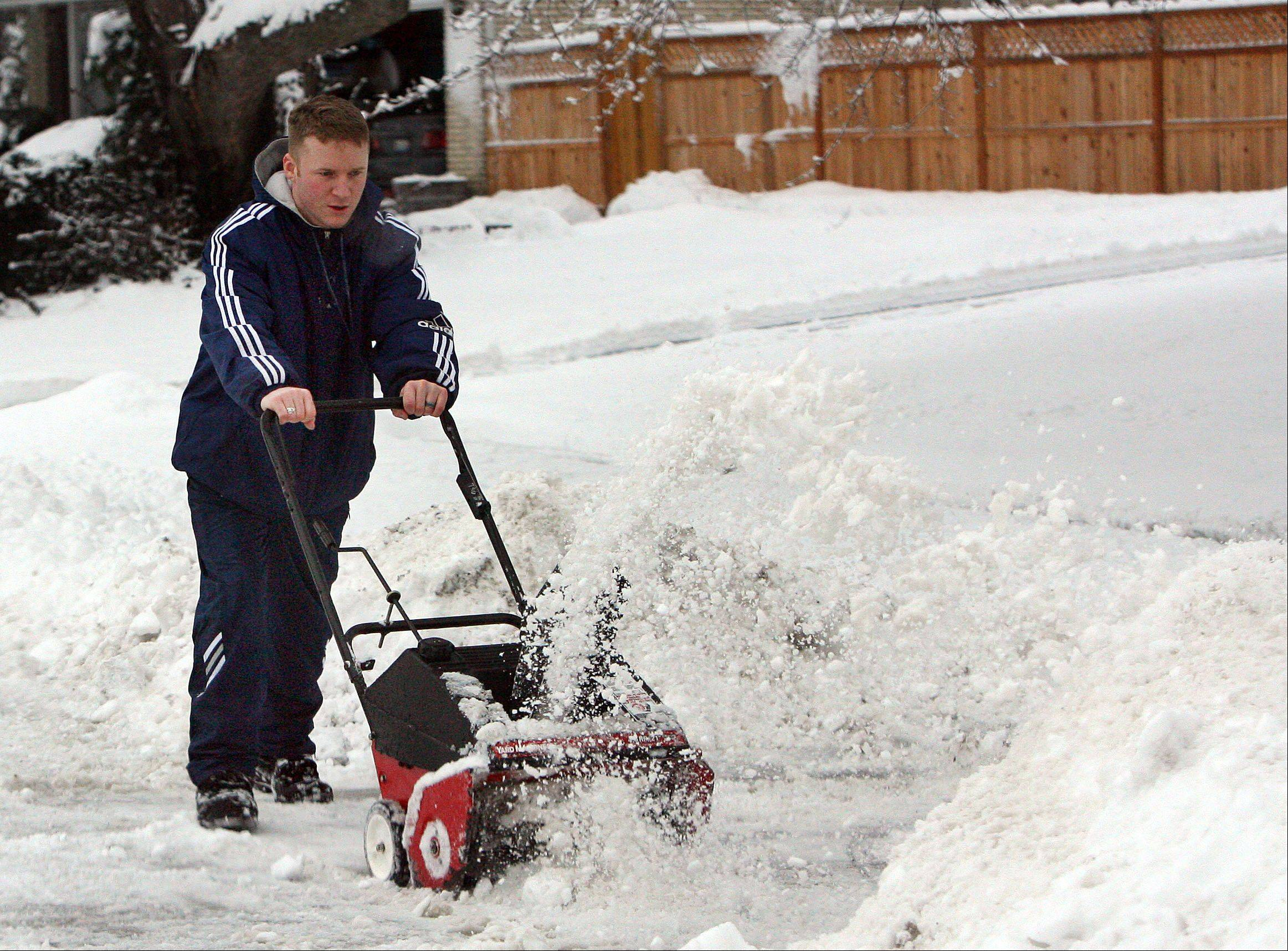 Brian Stith clears his driveway Friday morning in Mundelein after a winter storm hit the area Thursday night.