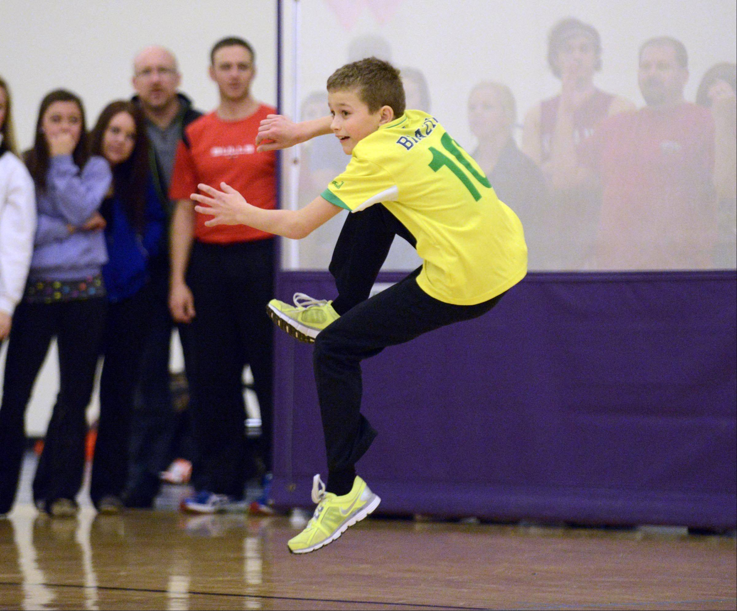 Thomas Mathson contorts himself to avoid getting hit during a dodgeball tournament at Hampshire High School Sunday. The 12-year-old was playing on a team of friends called Bananas in the fourth annual tournament to benefit local families in need. The Bananas won their first two games against much older teams of competitors.
