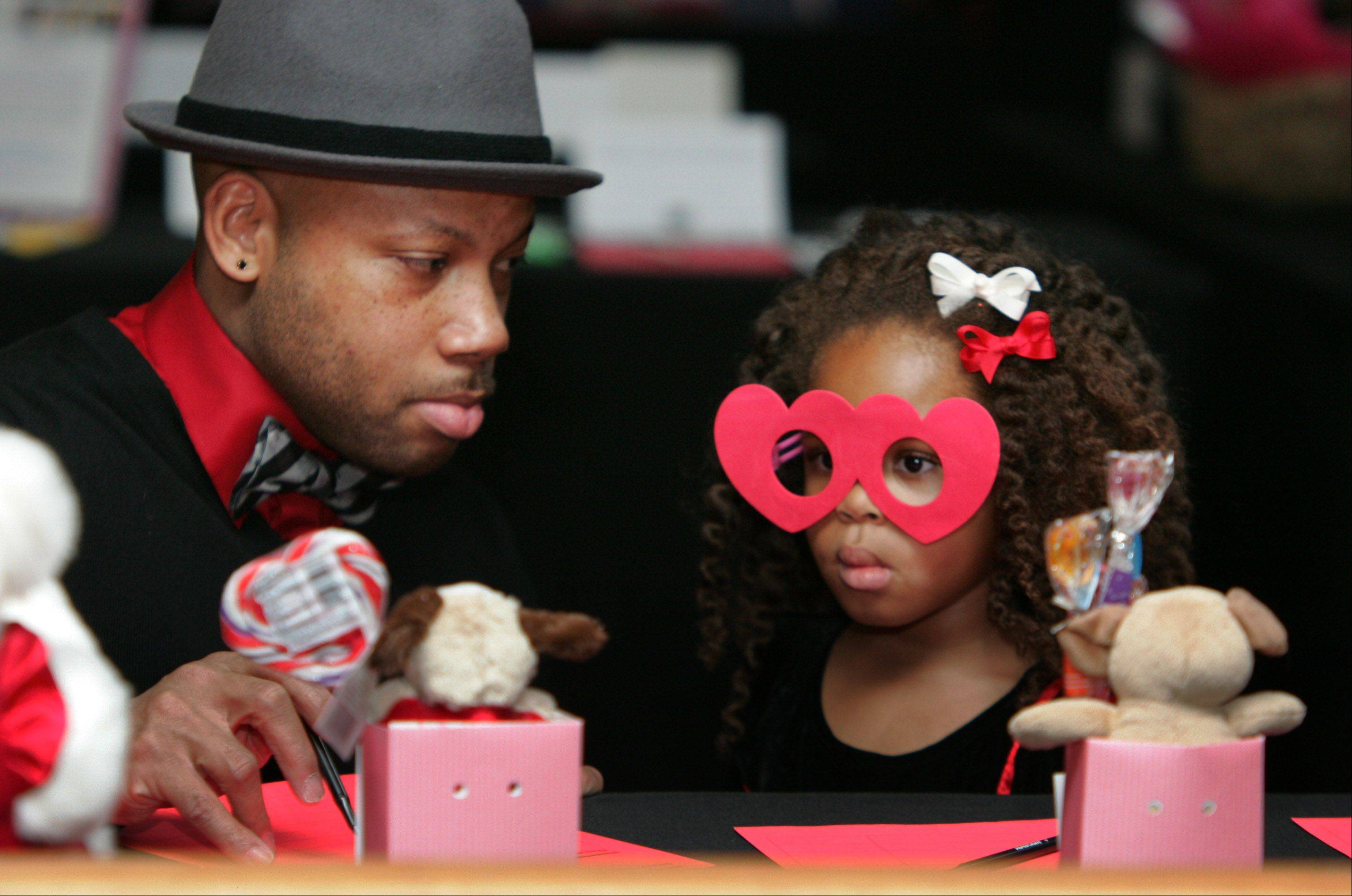 Tyrone Davis, of Great Lakes, looks at a silent auction with his daughter, Olivia, 4, during the Valentine's Dance Sunday at the Chevy Chase Country Club in Wheeling.
