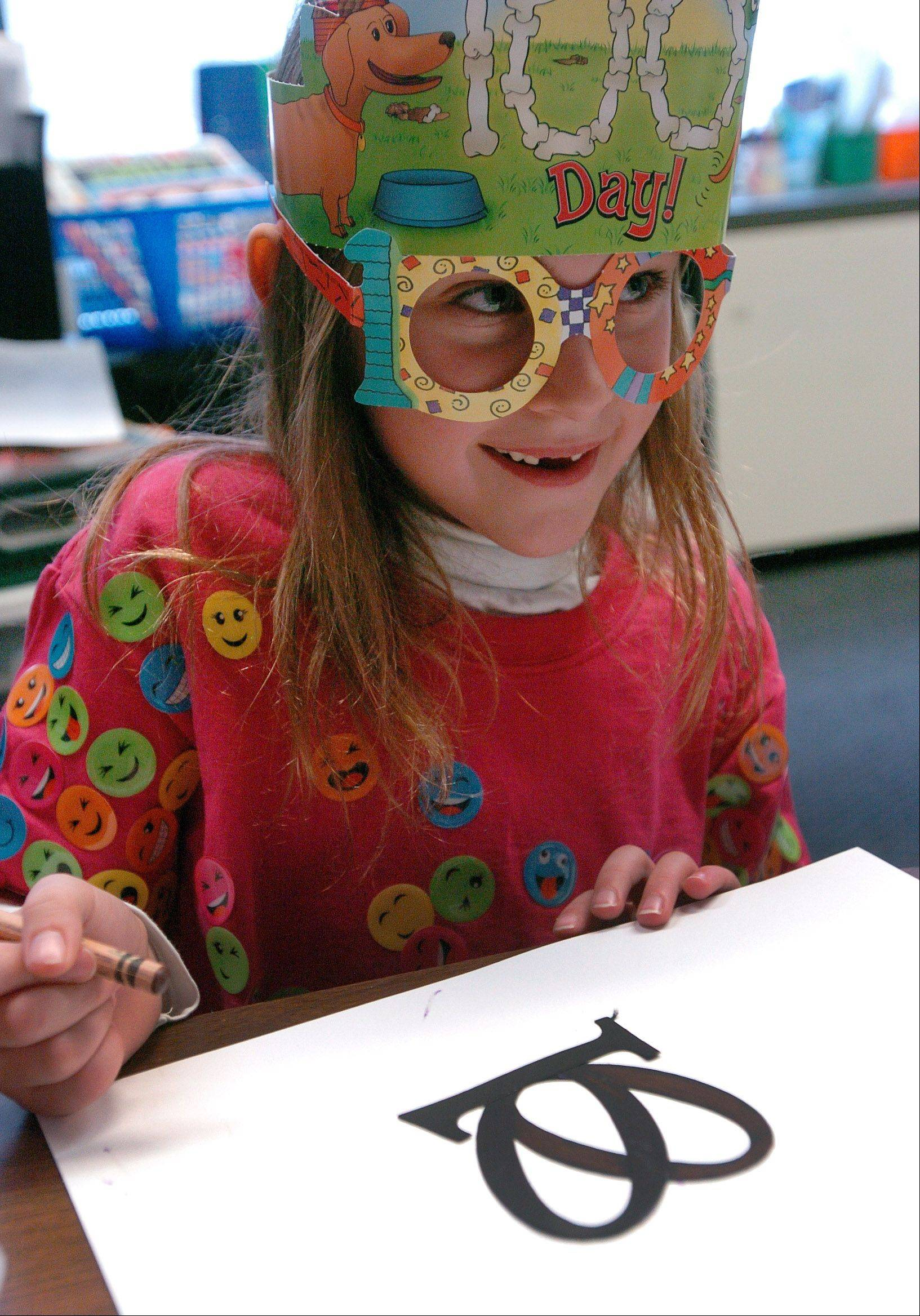 Rebecca Stephenson works on a drawing of a pretzel using the numerals 100, during Copeland Manor School celebration of the 100th day of school.