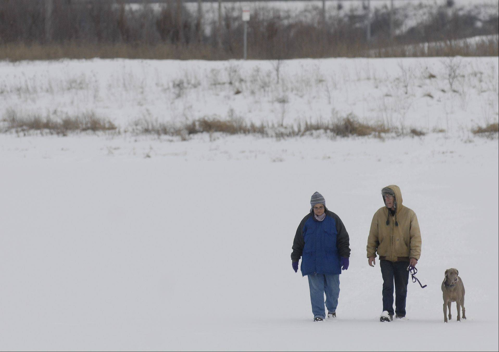 Marie and Steve Smith, of Lombard, walk with their dog April across the frozen lake at the East Branch forest preserve Wednesday.
