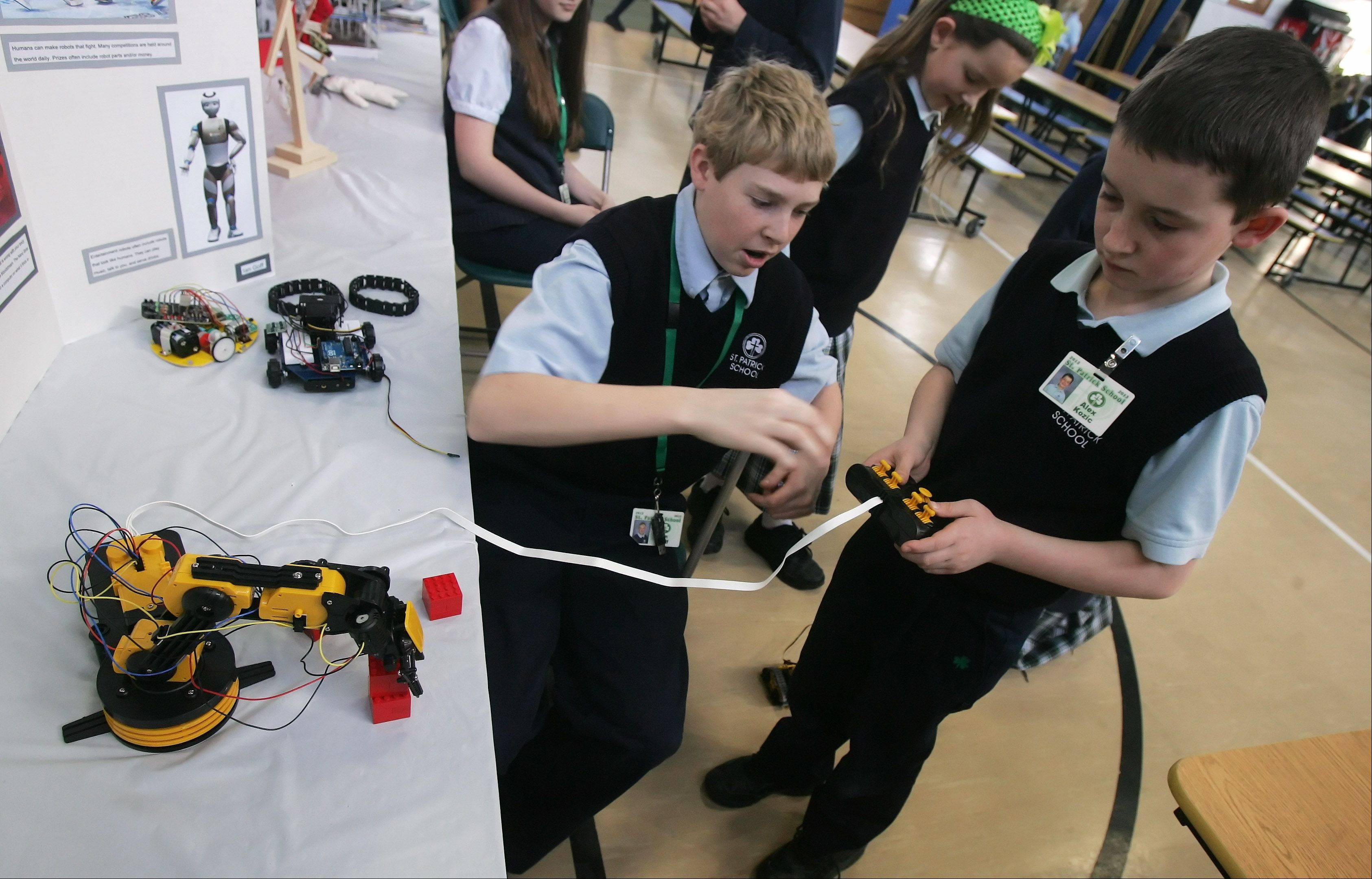 Eighth grader Ian Goff, left, helps fourth grader Alex Kozic operate a robot during the Academic Fair Wednesday at St. Patrick Catholic School in Wadsworth. Eighth grade students presented their projects on topics ranging from robotics, to Walt Disney World, to the Salem witch hunts.