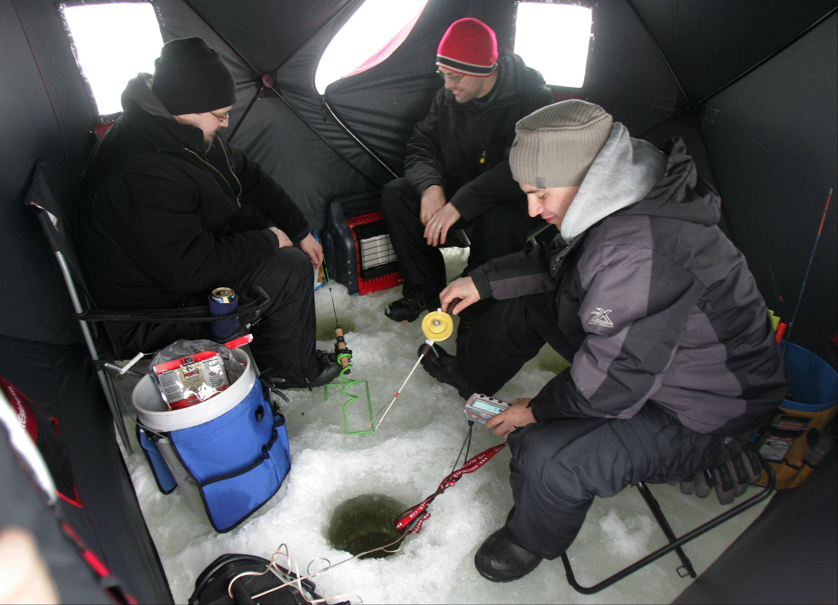 Matt Dee, of Grayslake, right, Joe Mazurkiewicz, of Hainesville, and his brother Chris, of Naperville, sit inside an ice shelter as they ice fish during the 53rd Annual Chain O'Lakes Ice Fishin' Derby and Winter Festival Sunday in Antioch. The Northern Illinois Conservation Club sponsored the event that featured a fishing tournament, raffle drawing, food and children's games.