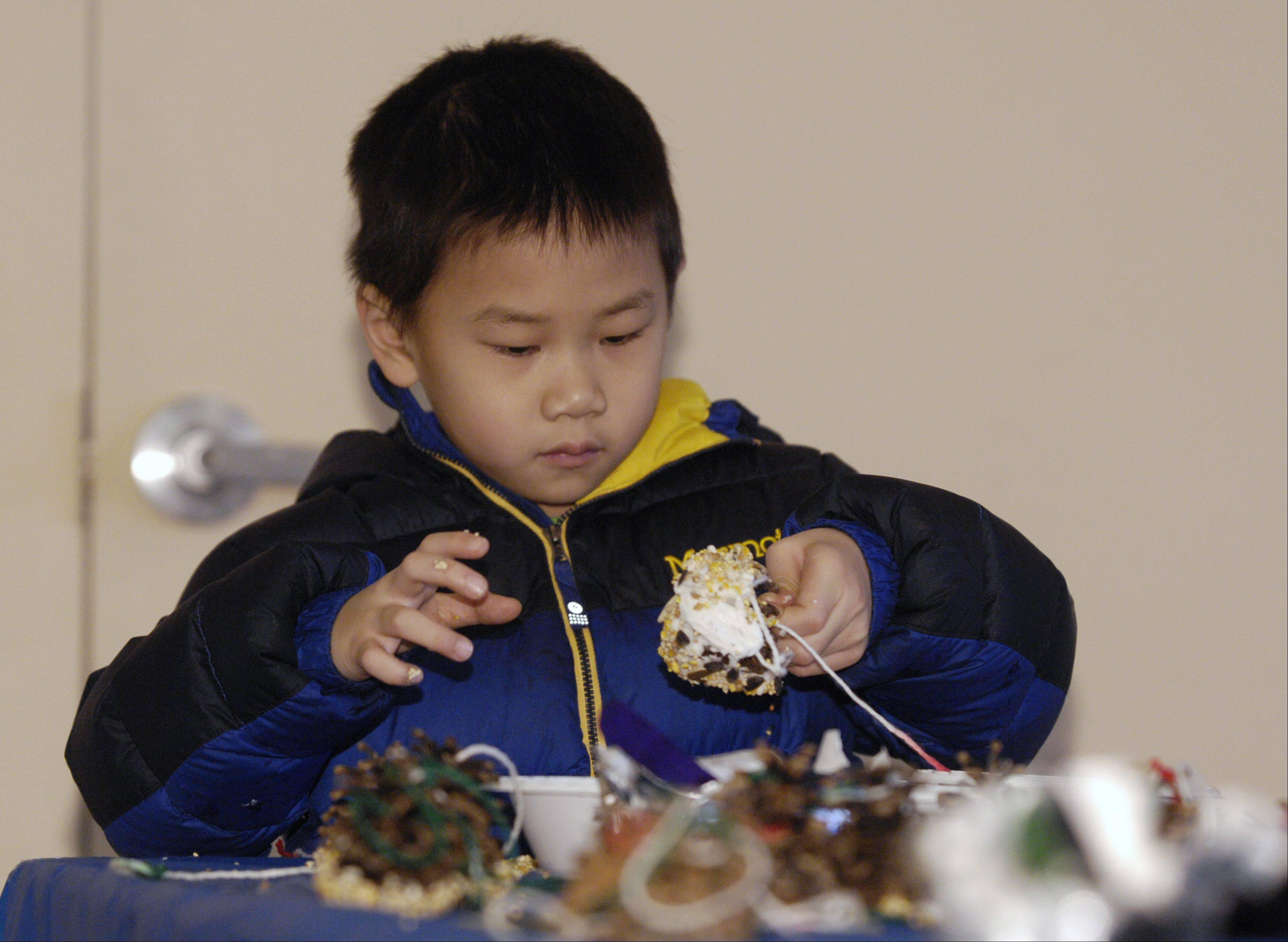 Christian Cheung, 5, of Oak Brook makes a pinecone bird feeder Sunday during the Oak Brook Park District and Oak Brook Civic Association's annual Winterfest at Central Park West.