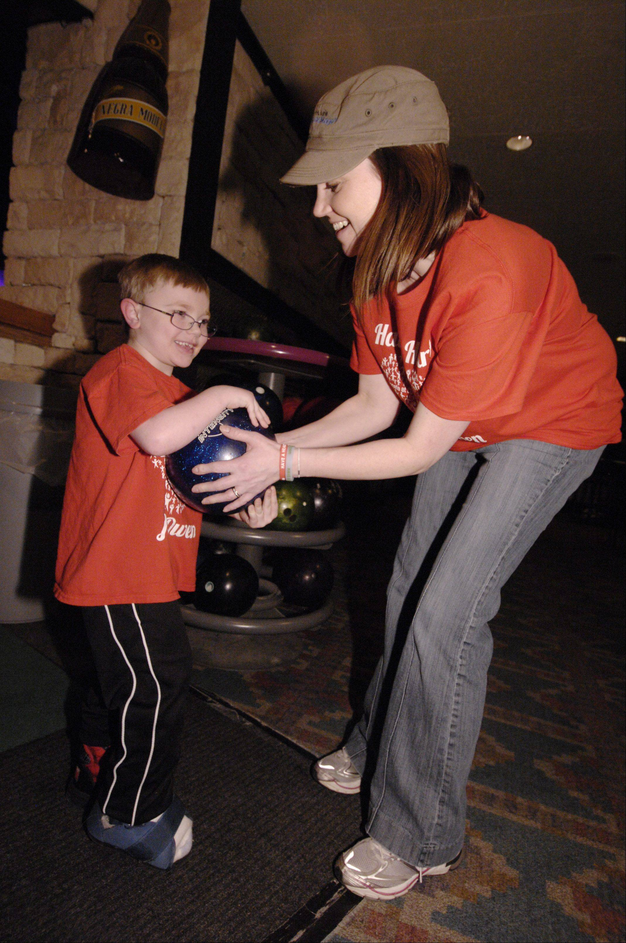 Owen Payton, 6, and his mother, Christina, of West Chicago, pick out a bowling ball during the Children's Organ Transplant Association's fundraiser for him Sunday at Bowling Green Sports Center. Owen, who was born with a congenital heart defect, is in need of a heart transplant.