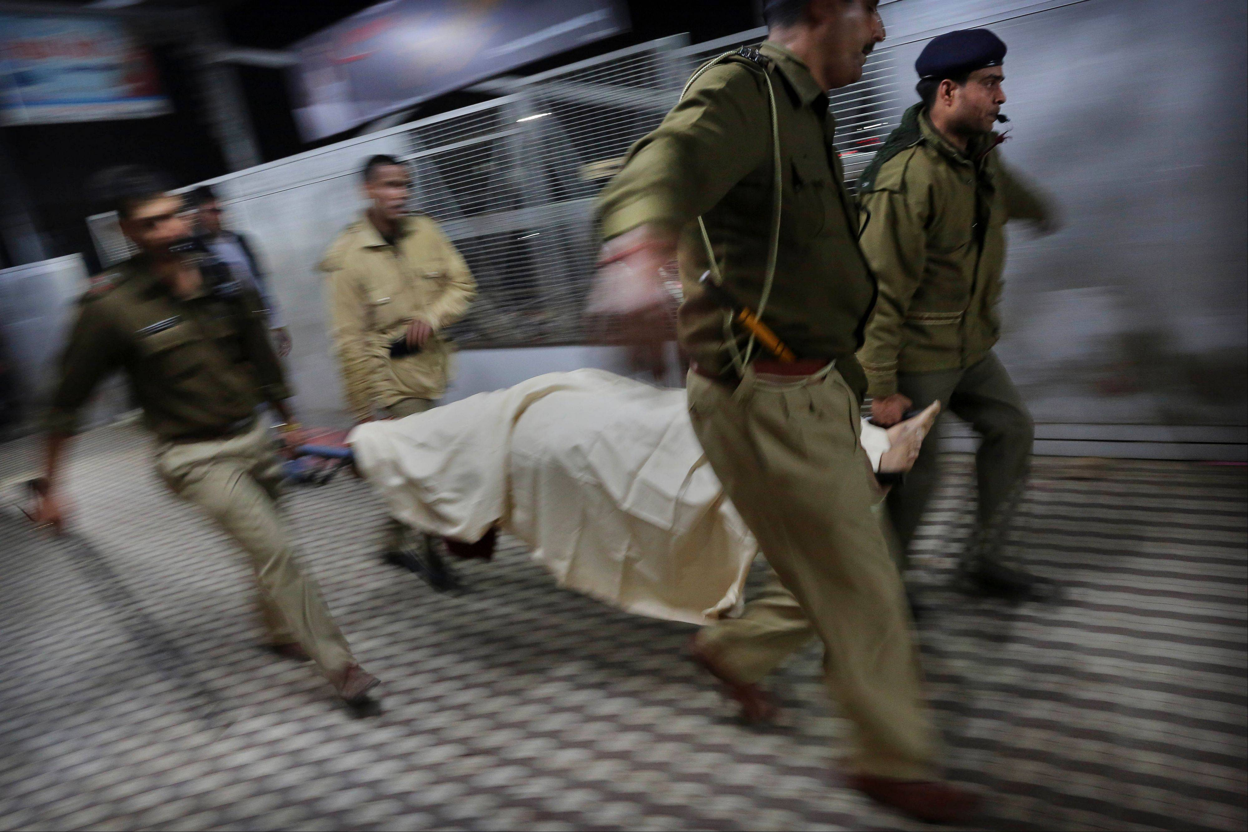 Indian police carry the body of a pilgrim who was killed in a stampede Sunday on a railway platform in Allahabad, India.