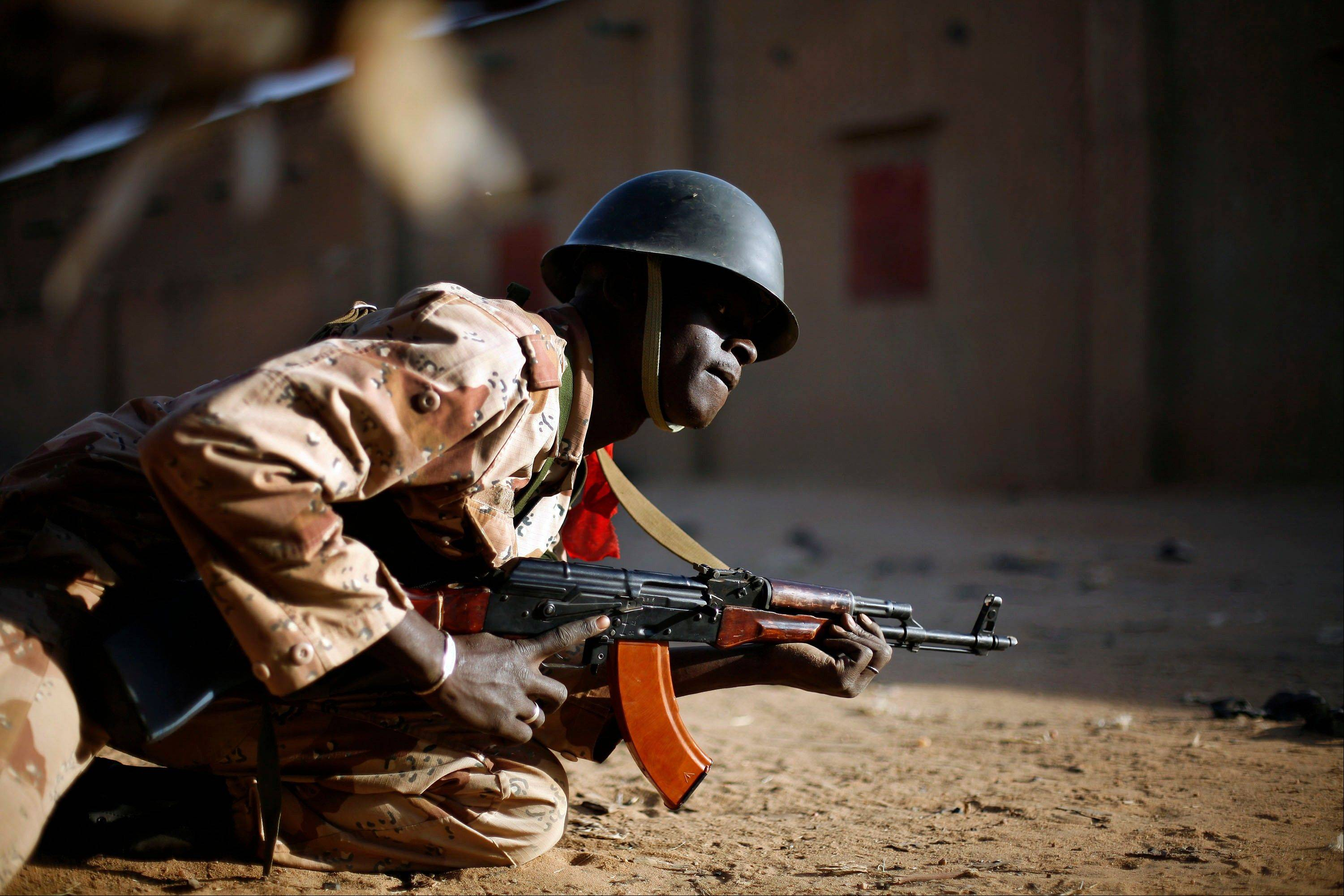 A Malian soldier takes cover behind a truck Sunday during exchanges of fire with jihadists in Gao.