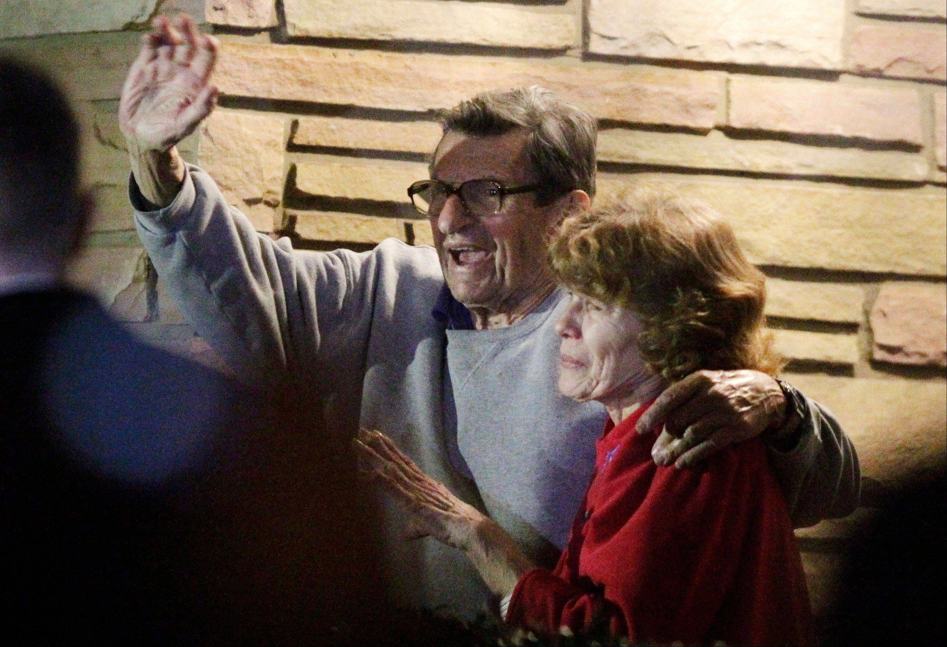 In this Nov. 9, 2011, photo, former Penn State coach Joe Paterno and his wife, Sue, stand on their porch to thank supporters gathered outside their home in State College, Pa. The Paterno family; s detailed response to a critical report on the handling of child abuse allegations against former assistant coach Jerry Sandusky has been released to the public.