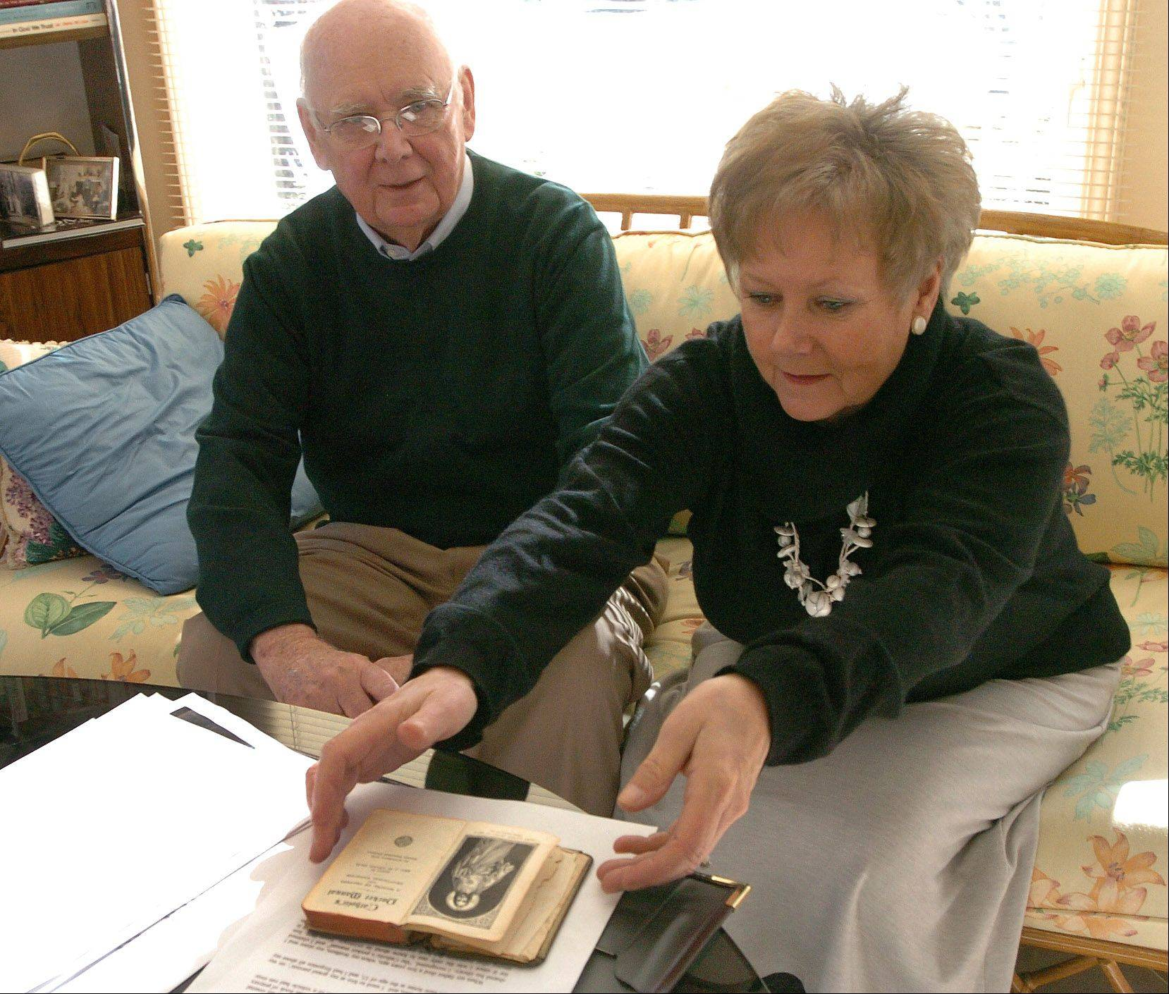 Ken Asmann and Marg Duer, with an American soldier's Catholic's Pocket Manual, which was found in France, and now returned to the States via Palatine's Sister City Fontenay-le-Comte.