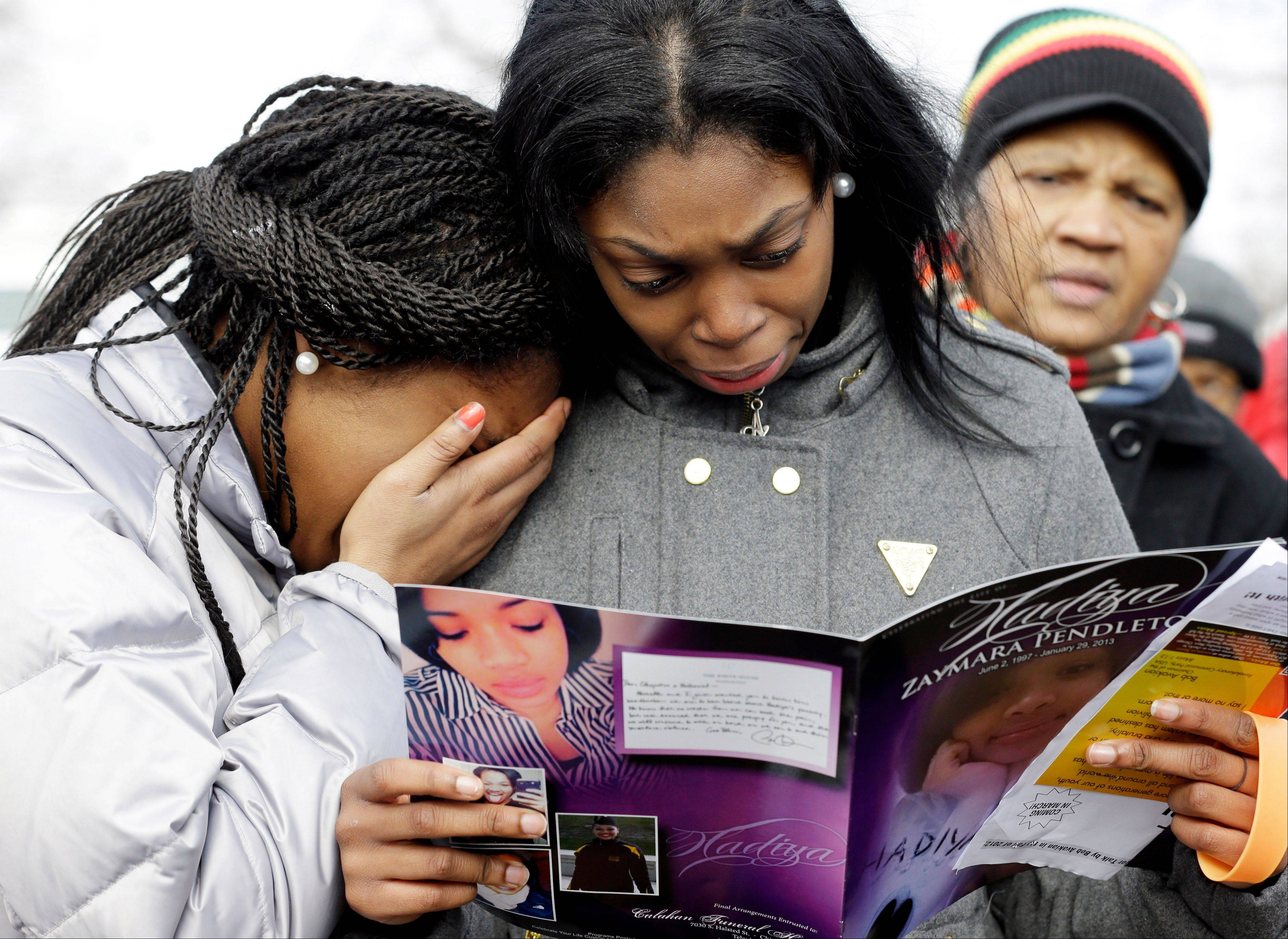 Danyia Bell, left 16, and Artureana Terrell , 16, react as they read a program for the funeral of Hadiya Pendleton outside the Greater Harvest Missionary Baptist Church after the funeral service of Hadiya Pendleton Saturday in Chicago. Hundreds of mourners and dignitaries including first lady Michelle Obama packed the funeral service Saturday for a Chicago teen whose killing catapulted her into the nation's debate over gun violence.