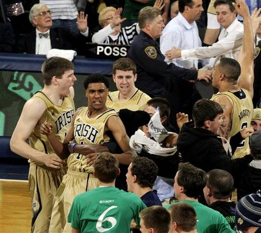 Notre Dame players including Cameron Biedscheid and Zach Auguste celebrate with fans following their 104-101 win against Louisville in the fifth overtime of their NCAA college basketball game, Saturday, Feb. 9, 2013, in South Bend, Ind. At top right, Louisville head coach Rick Pitino shakes hands with Notre Dame head coach Mike Brey.