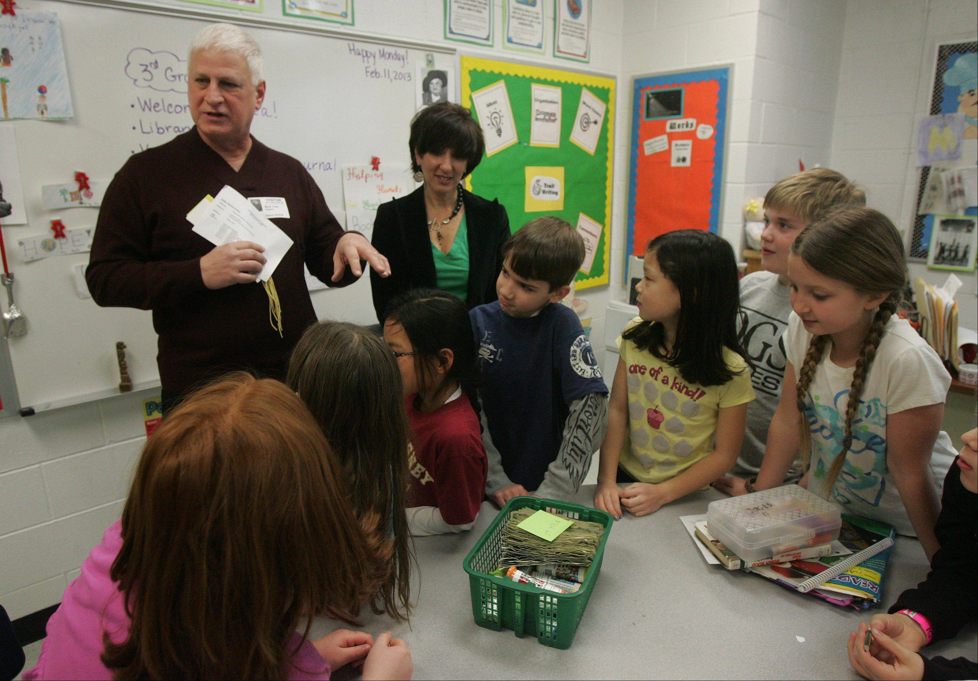 Mark Crea, CEO of Feed My Starving Children, thanks students during a visit to Maria Luce�s third-grade class Monday at Oak Grove School in Green Oaks. The students made and sold more than 2,000 bookmarks and raised $700 for the organization.