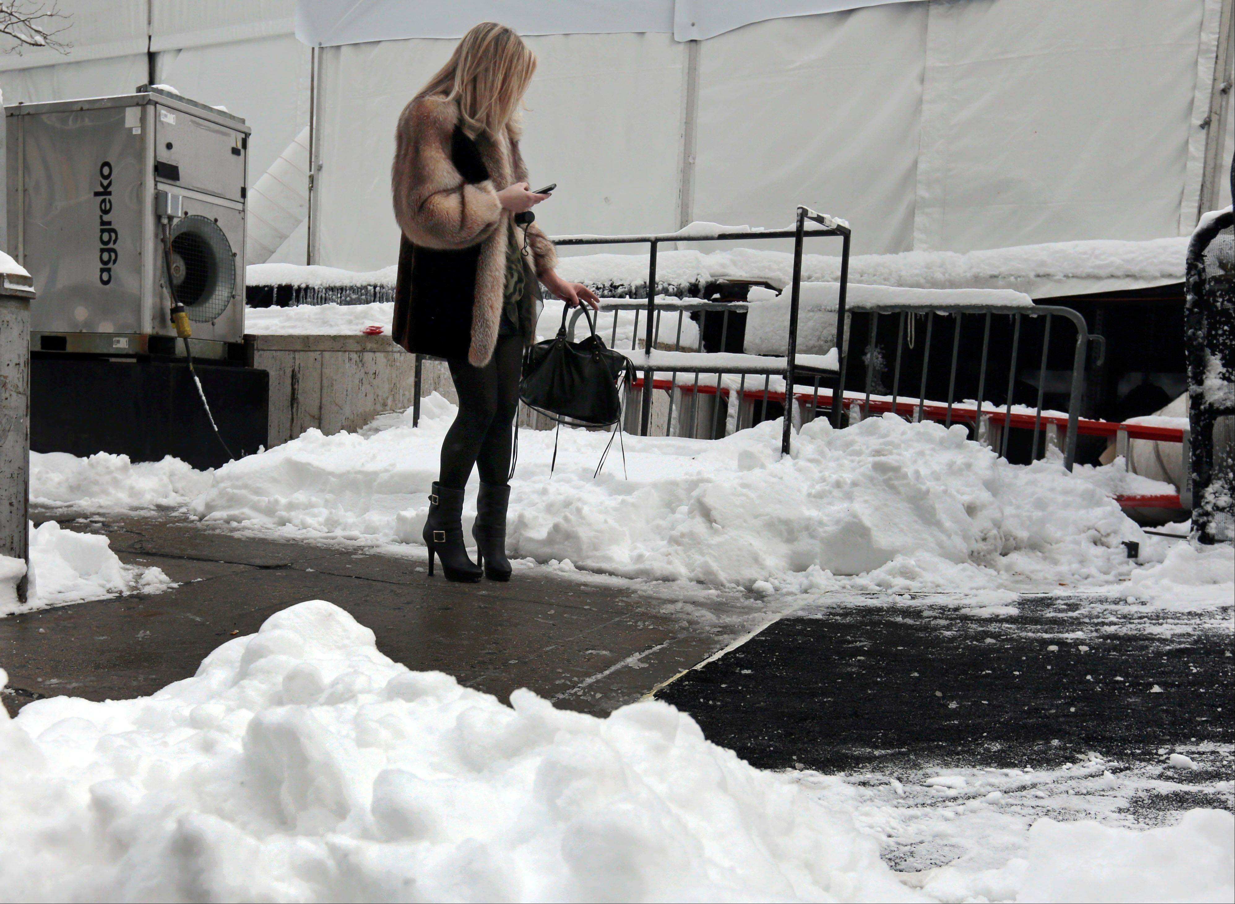 A woman checks her phone Saturday outside Lincoln Center in New York City. The snow total in Central Park was 8.1 inches by 3 a.m.