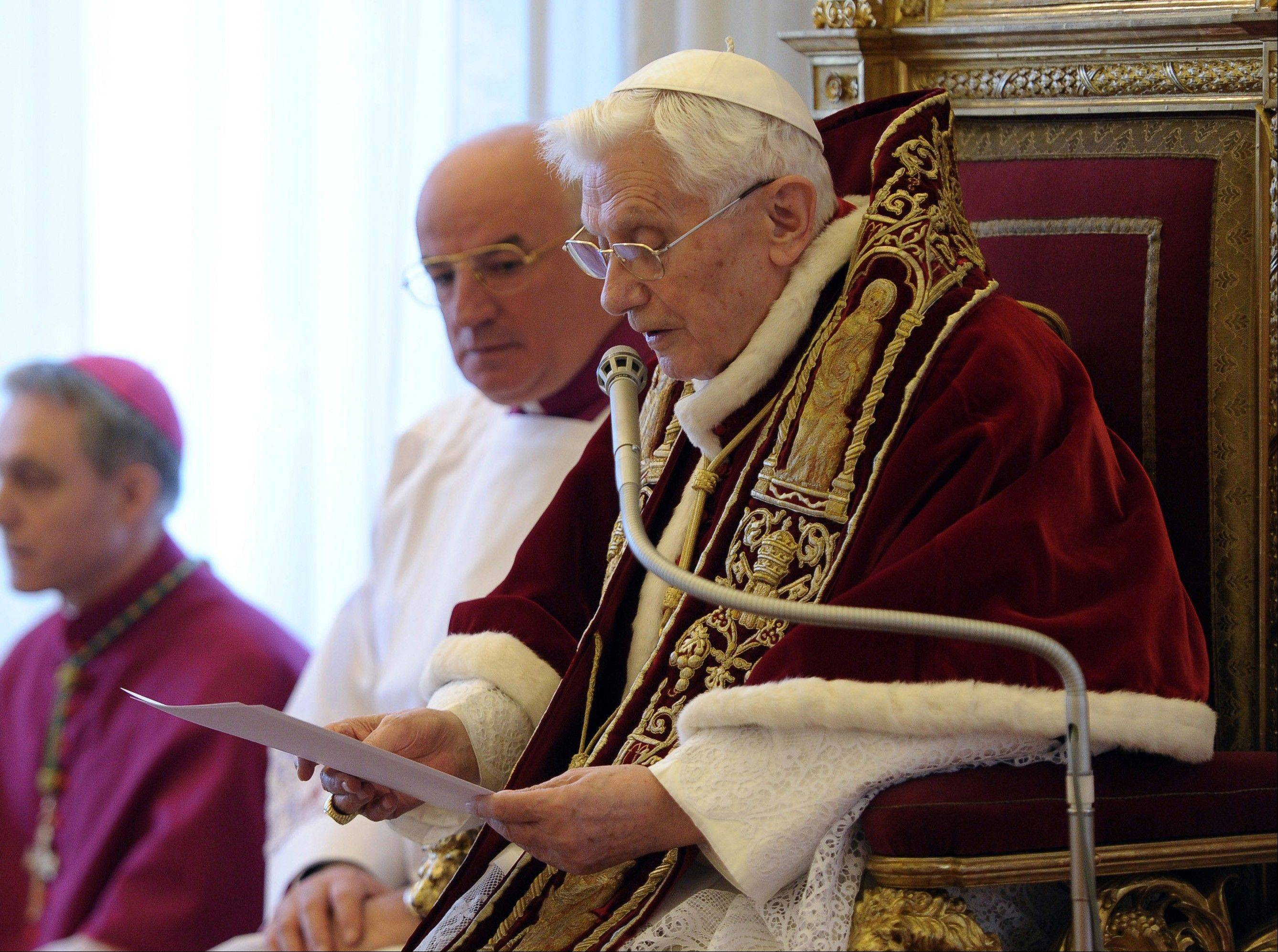 Pope Benedict XVI reads a document in Latin where he announces his resignation, during a meeting of Vatican cardinals at the Vatican Monday.