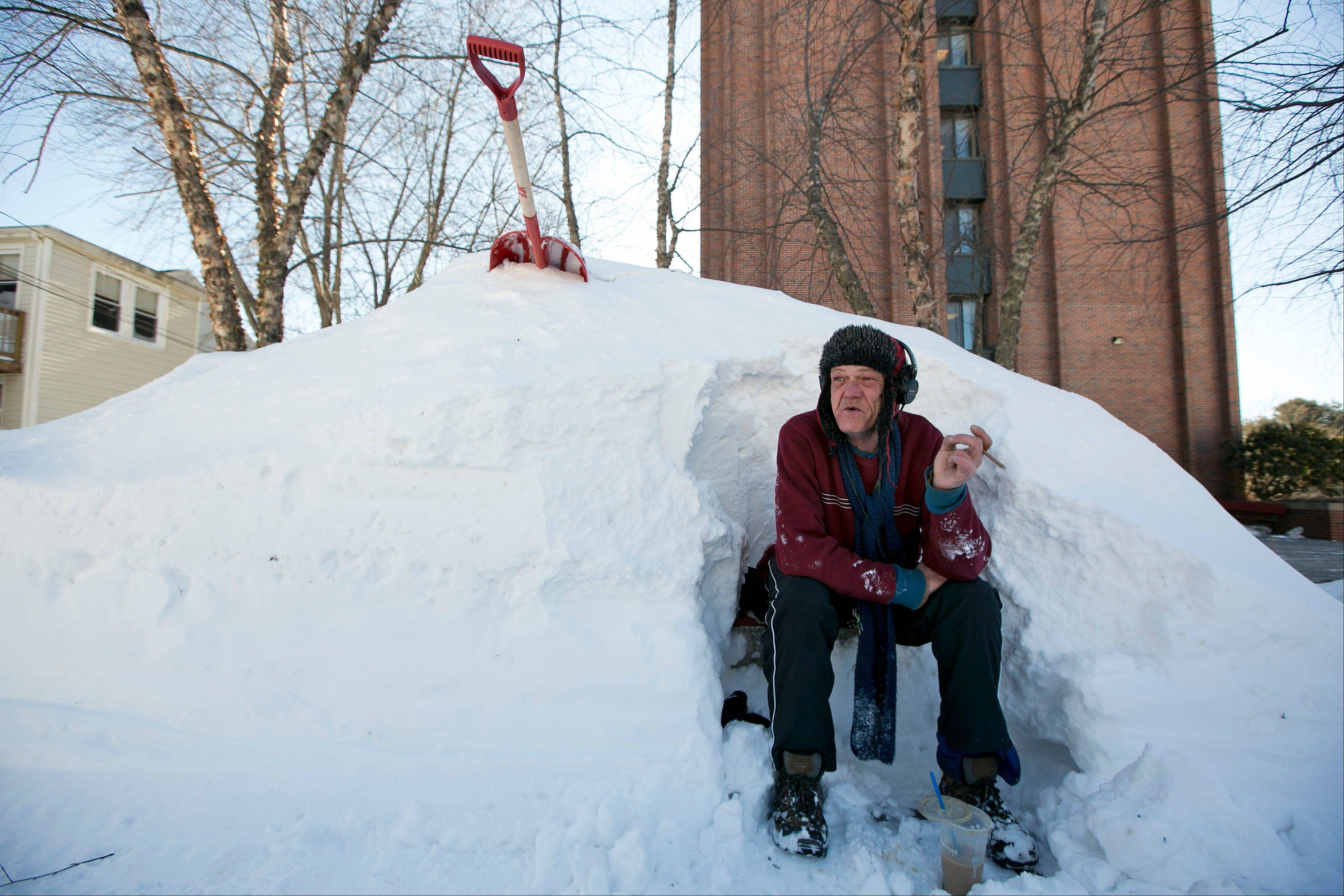 Bert Johnson takes a break while clearing snow from a bus stop bench outside the apartment complex where he lives in Portland, Maine, Sunday.