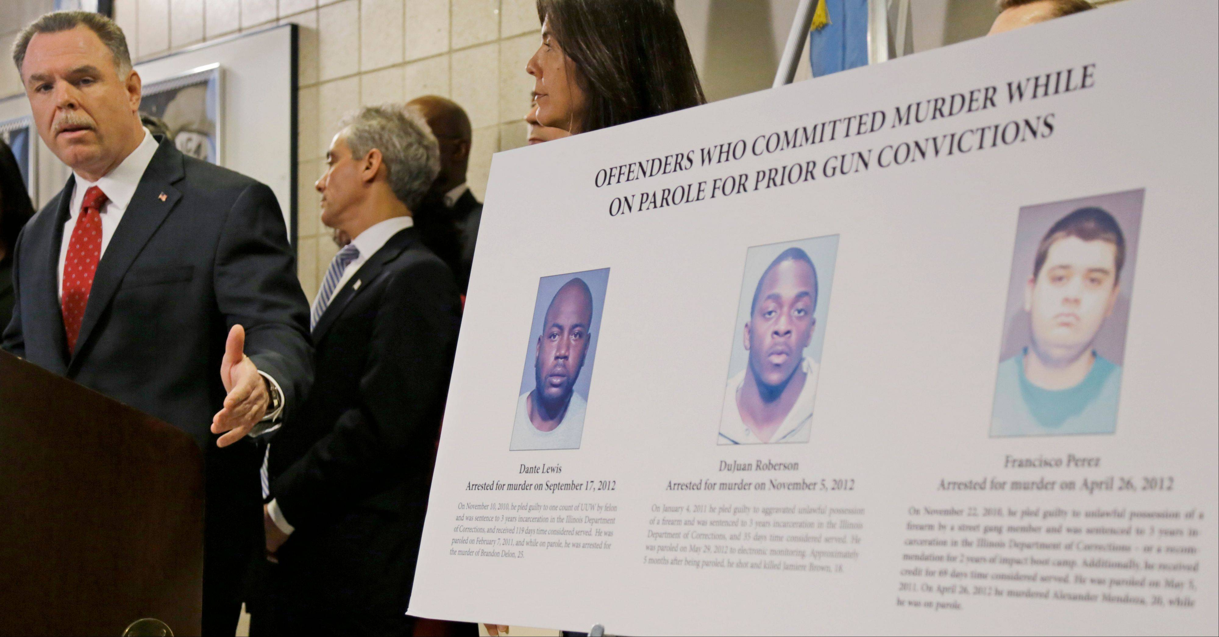 During a news conference Monday, Chicago Police Superintendent Garry McCarthy points to a poster showing three people who committed murders while on parole for prior gun convictions.
