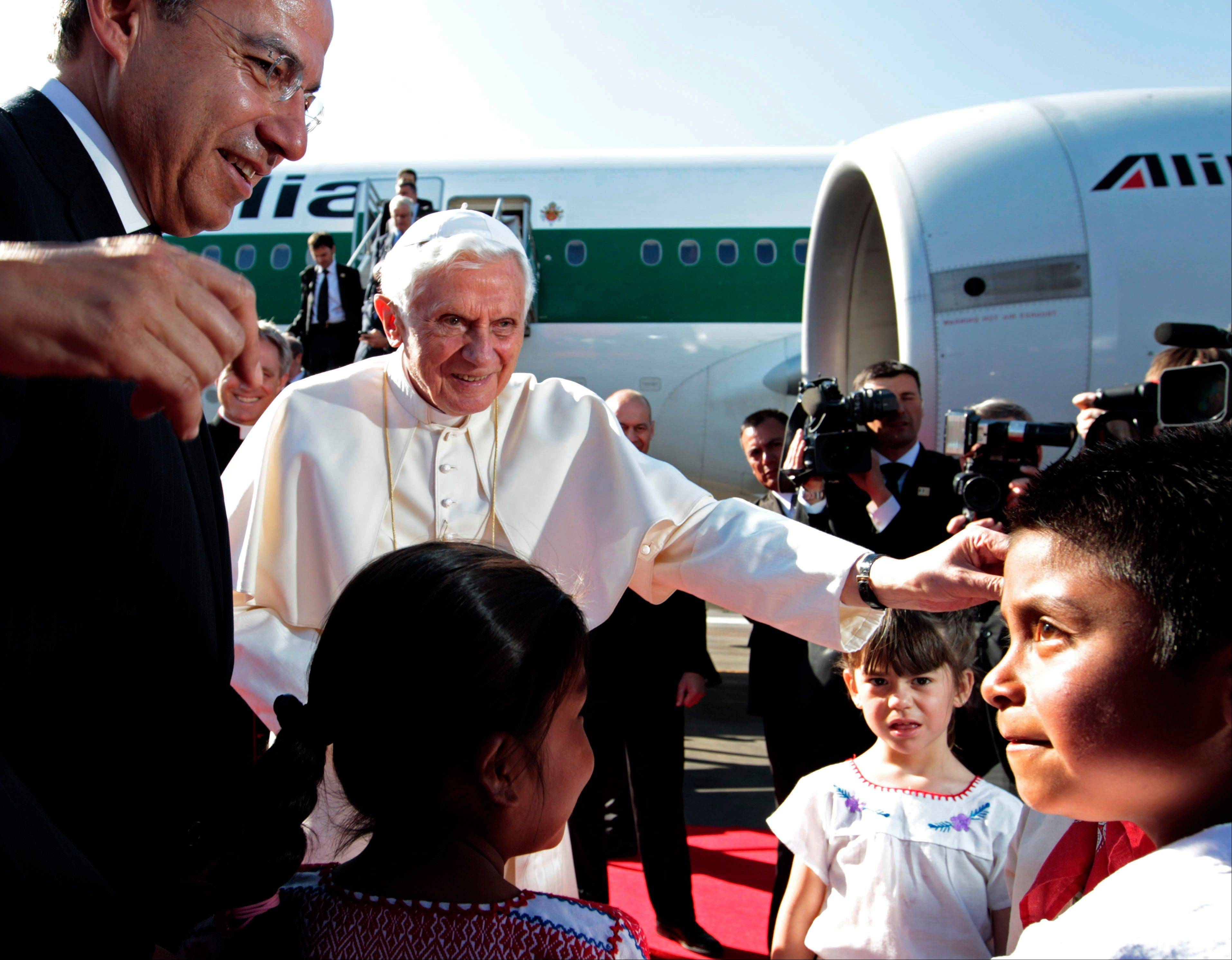 Mexico's President Felipe Calderon, left, looks on as Pope Benedict XVI is greeted by children at the airport in Silao, Mexico, his first to the country. Pope Benedict XVI announced Monday he would resign Feb. 28 because he is simply too old to carry on.