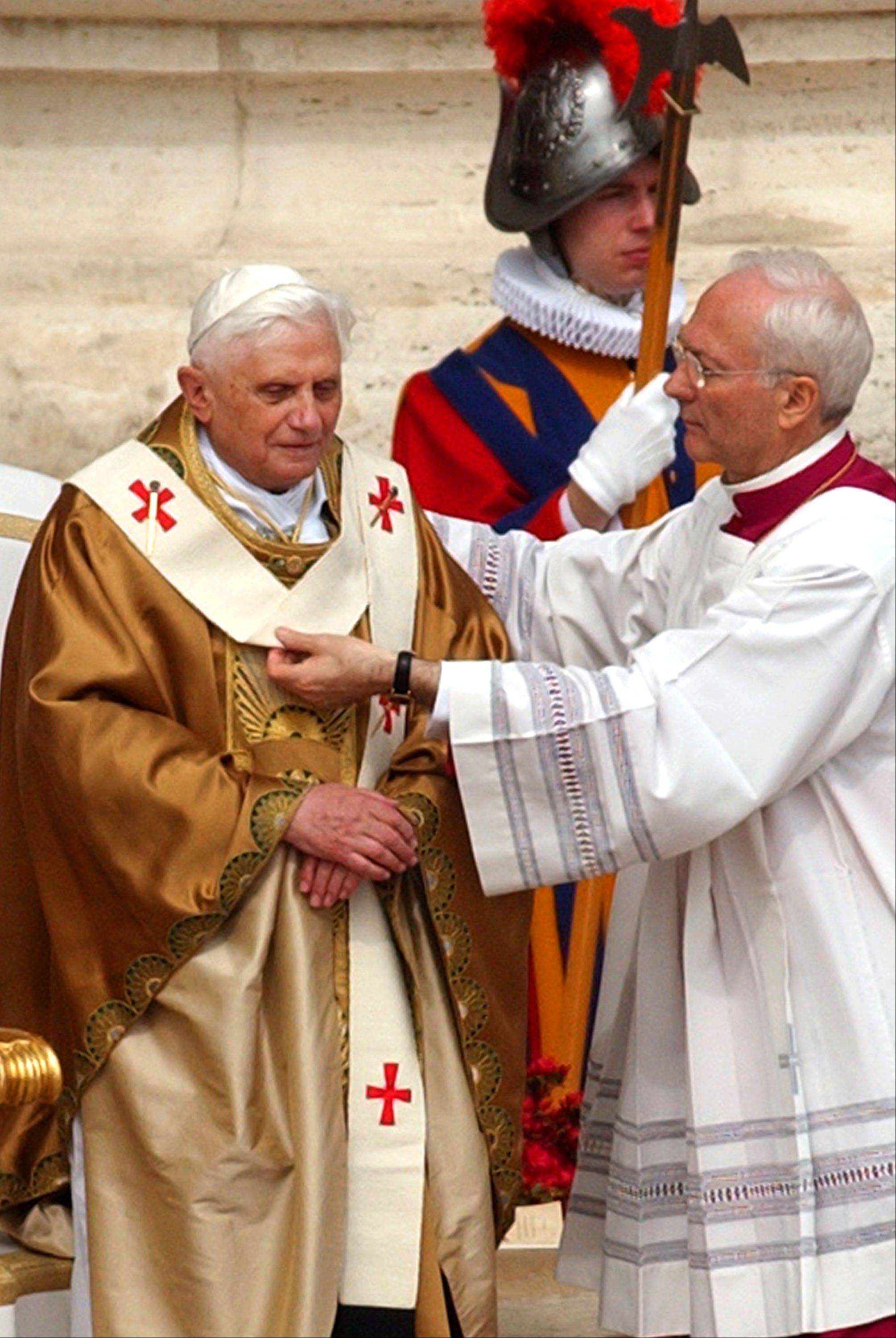 Archbishop Piero Marini drapes Pope Benedict XVI with the pallium during his installment Mass in St. Peter's Square at the Vatican.