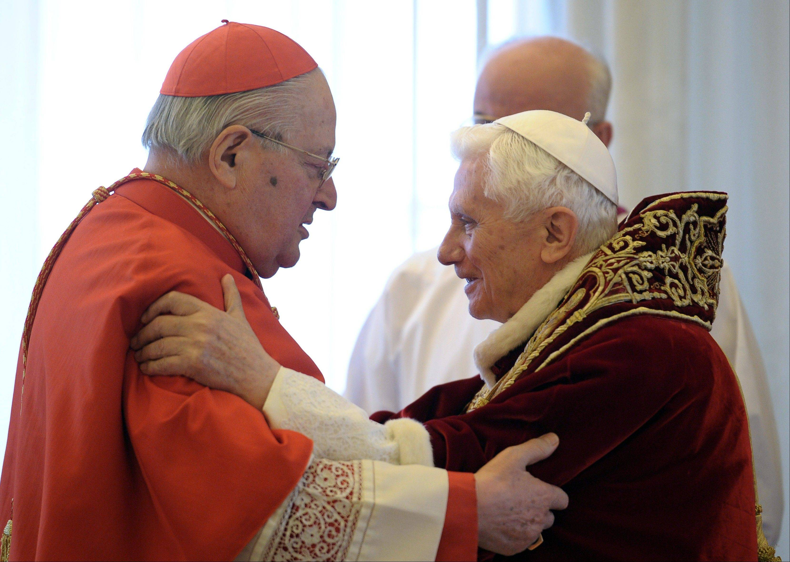 Pope Benedict XVI, right, and Cardinal Angelo Sodano, Dean of the College of Cardinals, hug each other after the pontiff announced Monday during the meeting of Vatican cardinals that he would resign on Feb. 28.