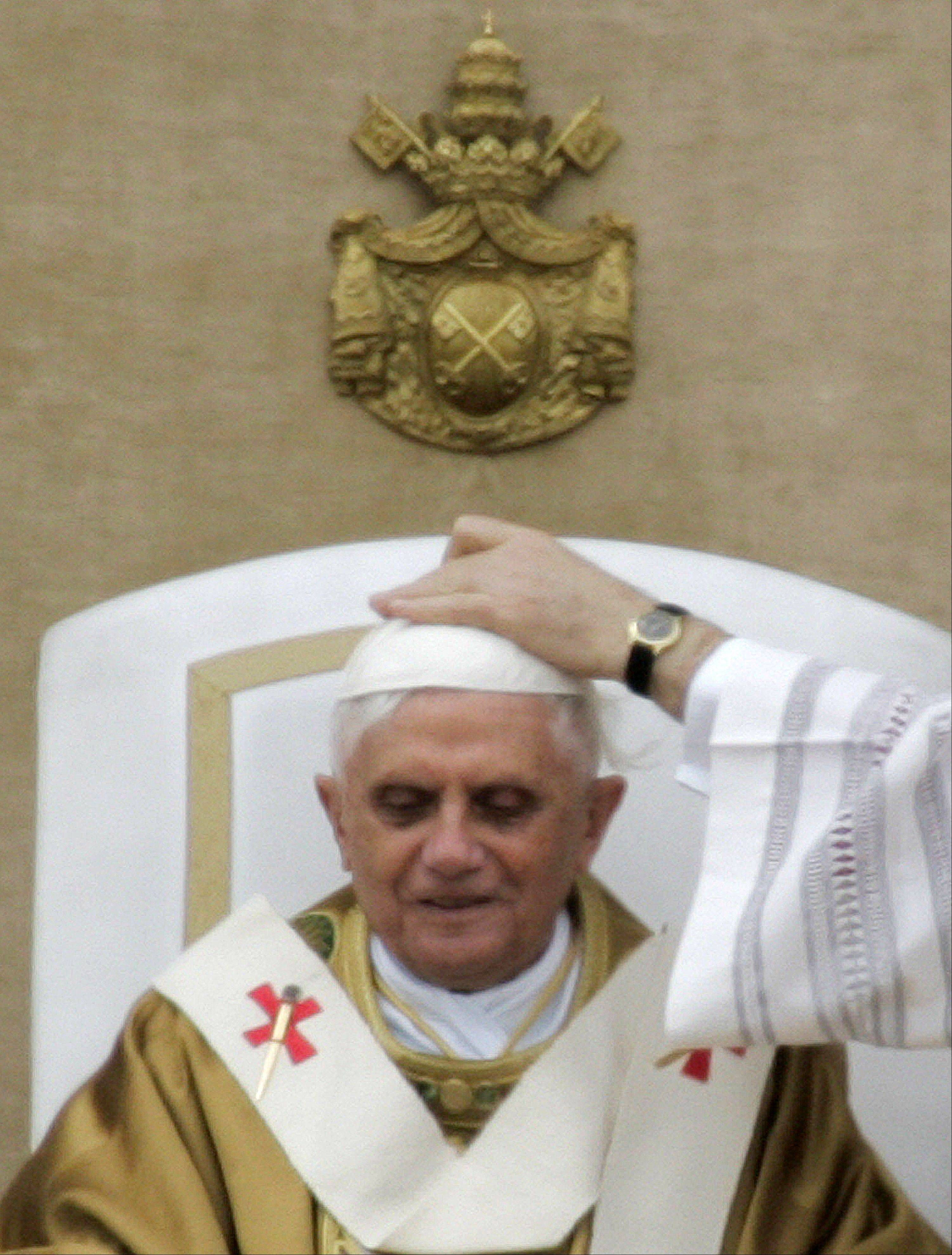 Vatican master of Ceremonies Archbishop Piero Marini, not pictured, adjusts the skullcap of Pope Benedict XVI during his installment Mass in St. Peter's Square at the Vatican.