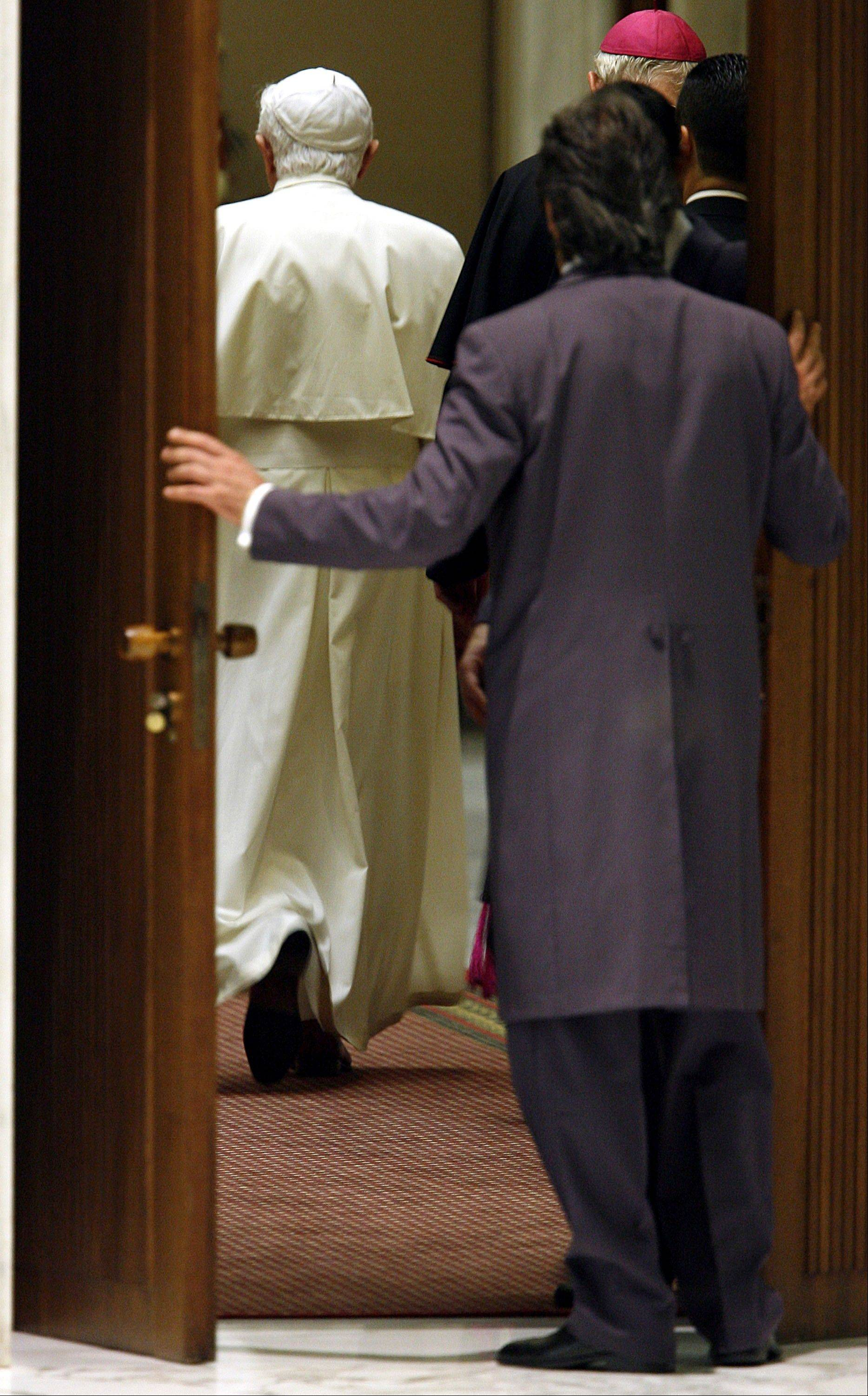 A Vatican usher, foreground, closes a door as Pope Benedict XVI leaves after an audience in Pope Paul VI hall at the Vatican.