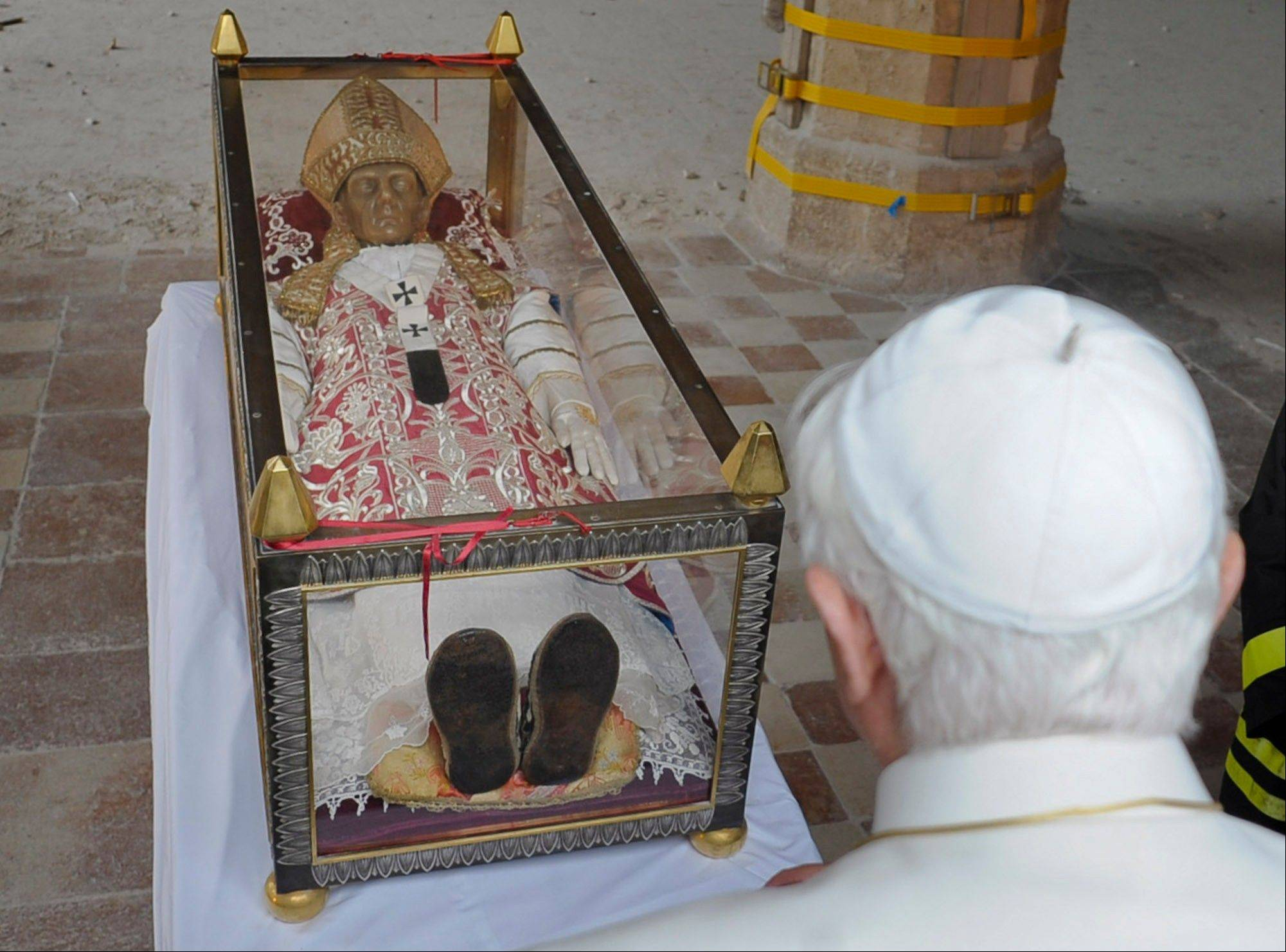 Pope Benedict XVI stands by the salvaged remains of Pope Celestine V in the 13th-century Santa Maria di Collemaggio Basilica, the symbol of the city of L'Aquila, whose roof partially caved in during an earthquake.