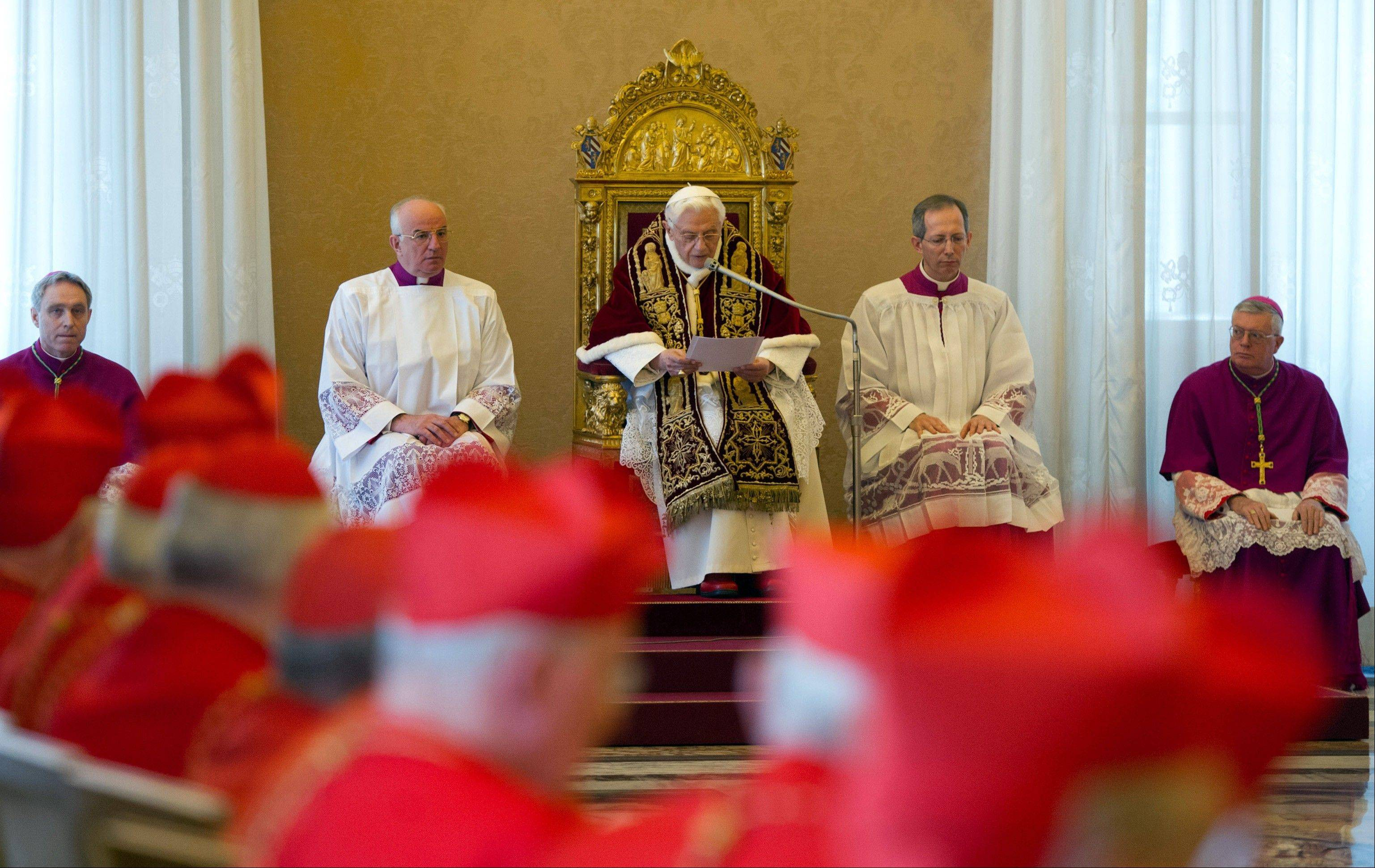 Pope Benedict XVI, center, reads a document in Latin where he announces his resignation Monday during a meeting of Vatican cardinals.