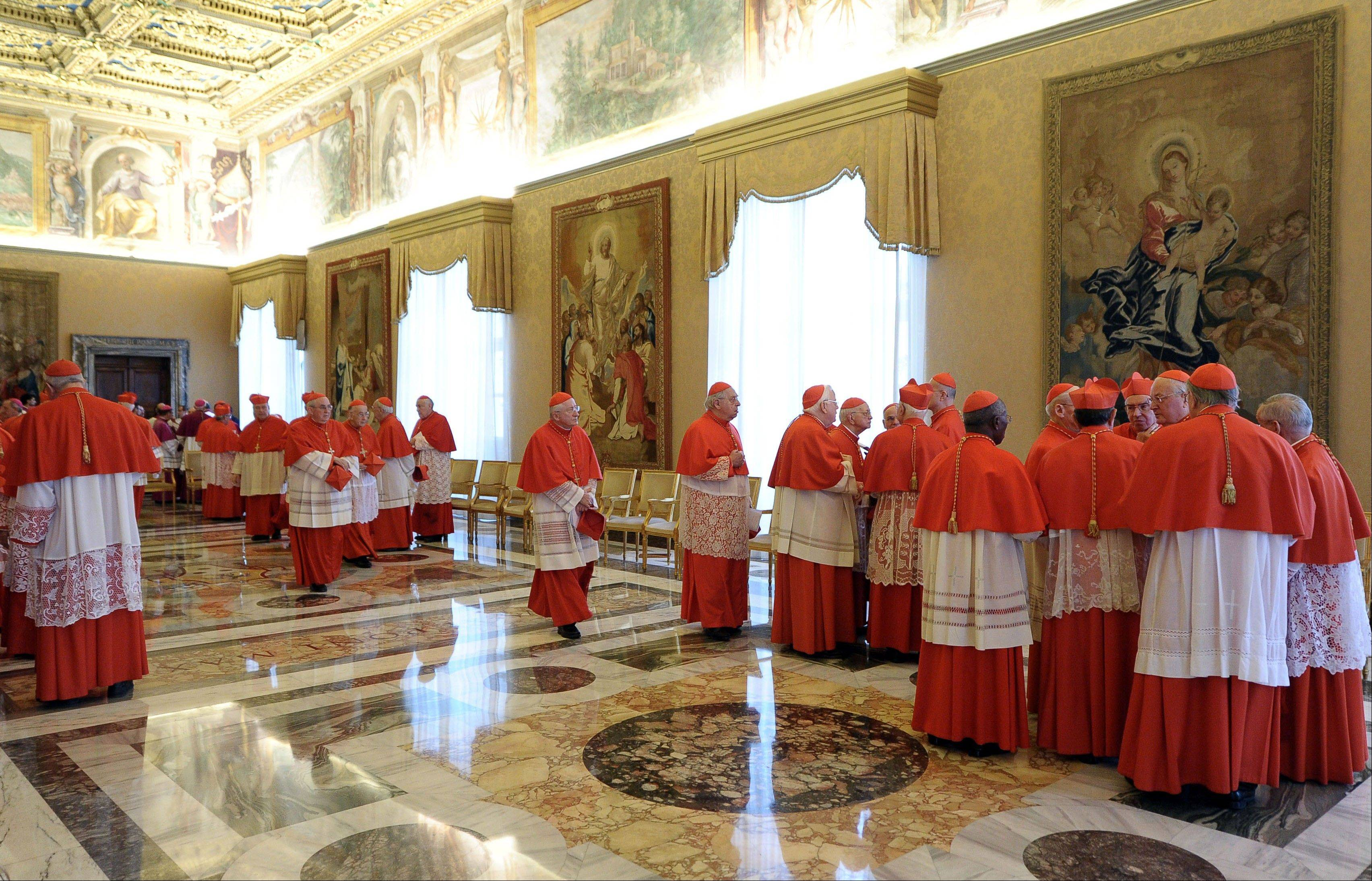 Cardinals talk among themselves after Pope Benedict XVI, not pictured, announced his resignation Monday during a meeting with the cardinals, at the Vatican. The decision sets the stage for a conclave to elect a new pope before the end of March.