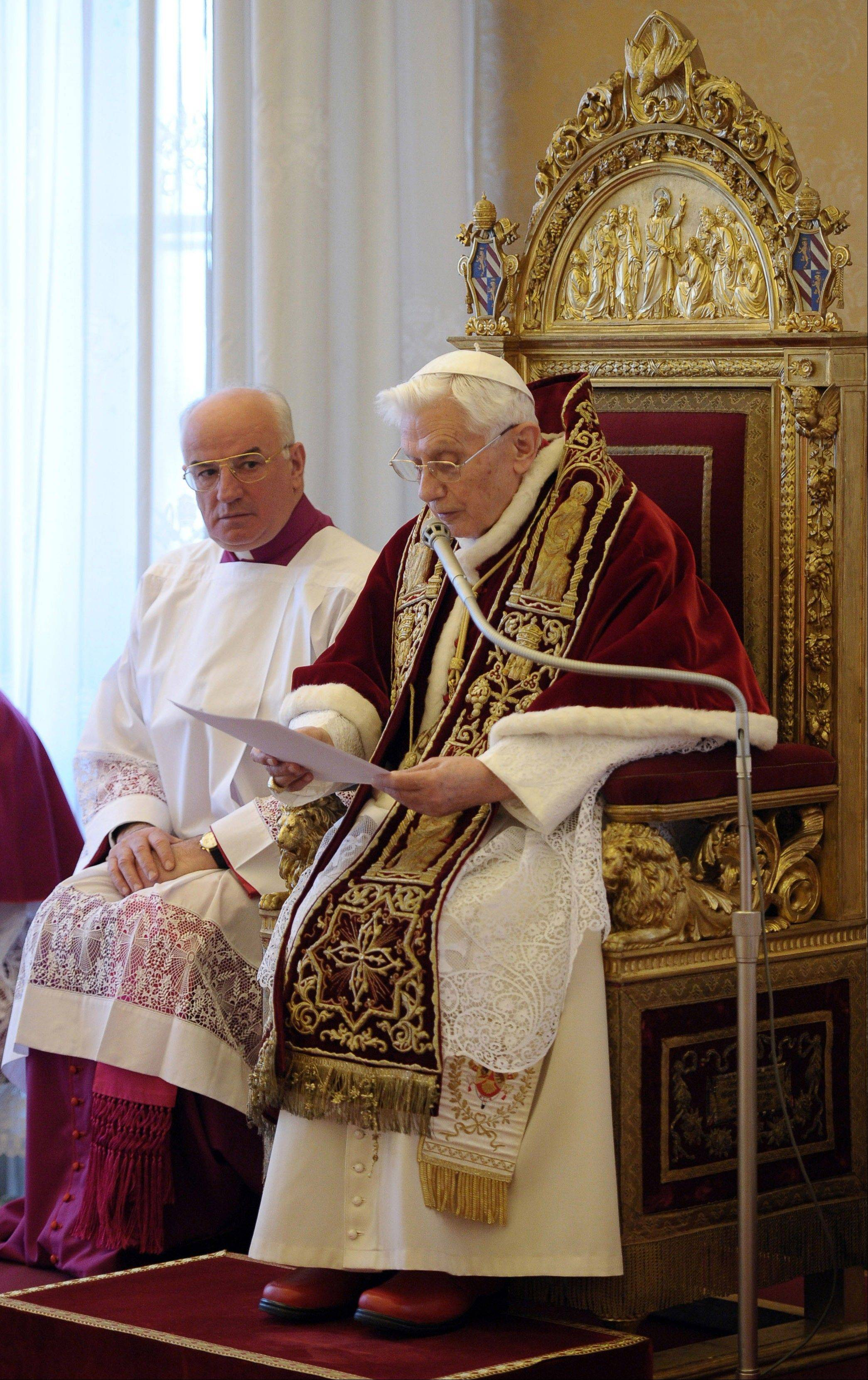 Mons. Franco Comaldo, a pope aide, left, looks at Pope Benedict XVI as he reads a document in Latin where he announces his resignation Monday during a meeting of Vatican cardinals at the Vatican.