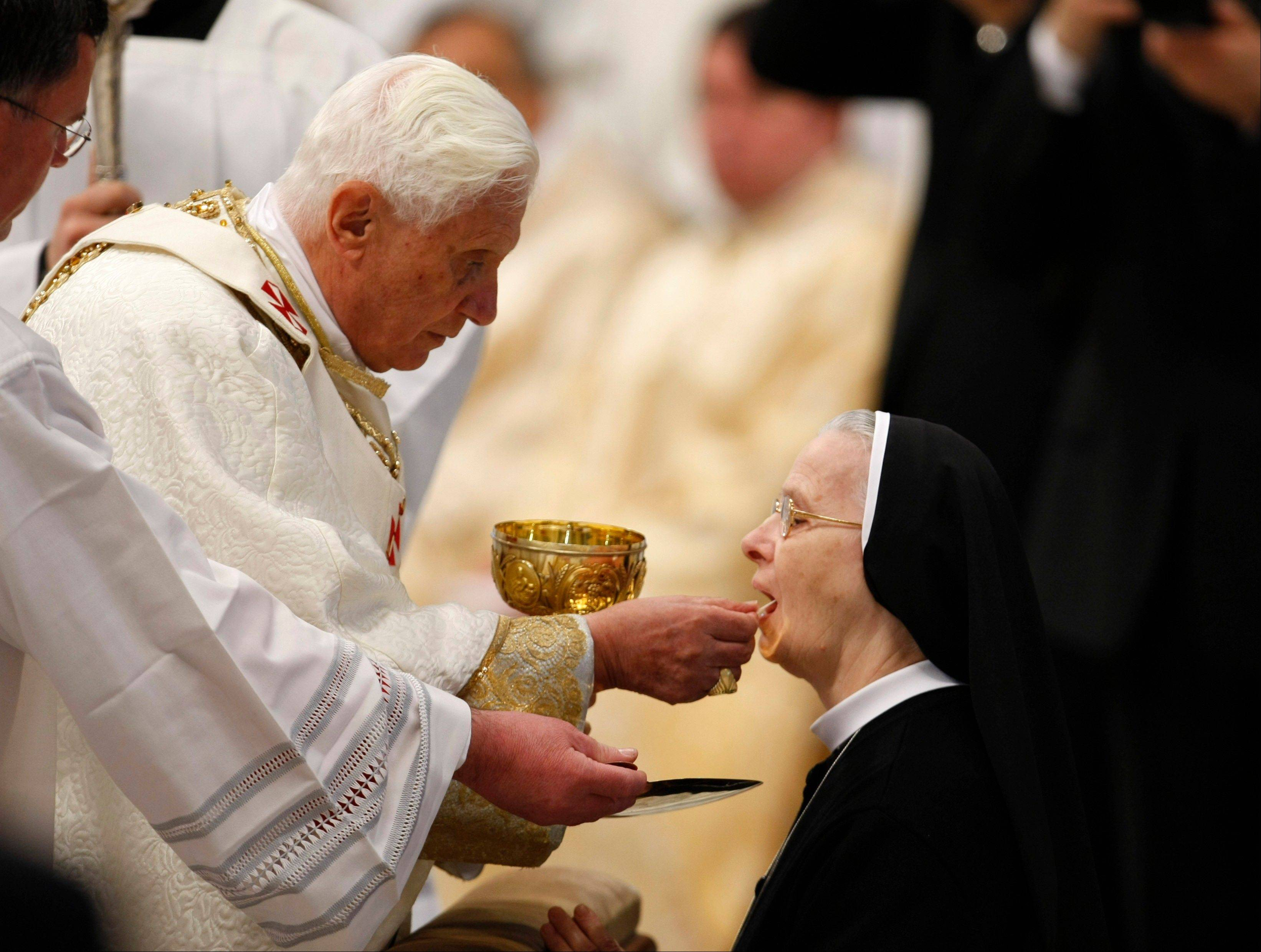Pope Benedict XVI offers a nun the Holy Communion, a Chrism Mass inside St. Peter's Basilica at the Vatican, as Benedict XVI celebrated a Holy Thursday Mass that included the traditional blessing of holy oils -- some of which the church will send to an earthquake zone as a sign of closeness to the stricken population.