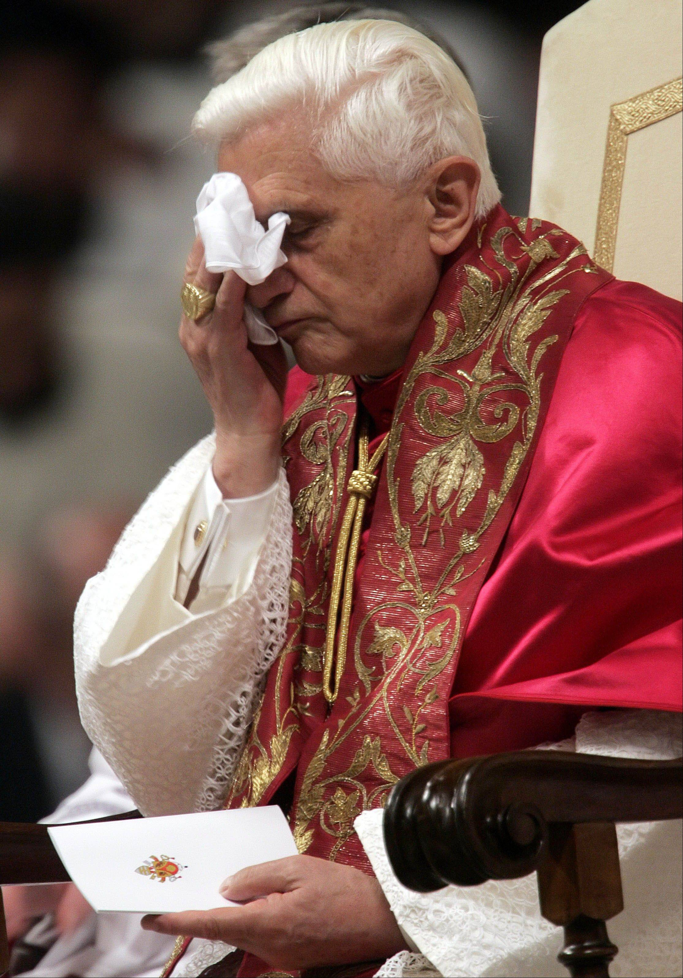 Pope Benedict XVI wipes his face during a solemn adoration of the Eucharist in St. Peter's Basilica at the Vatican.