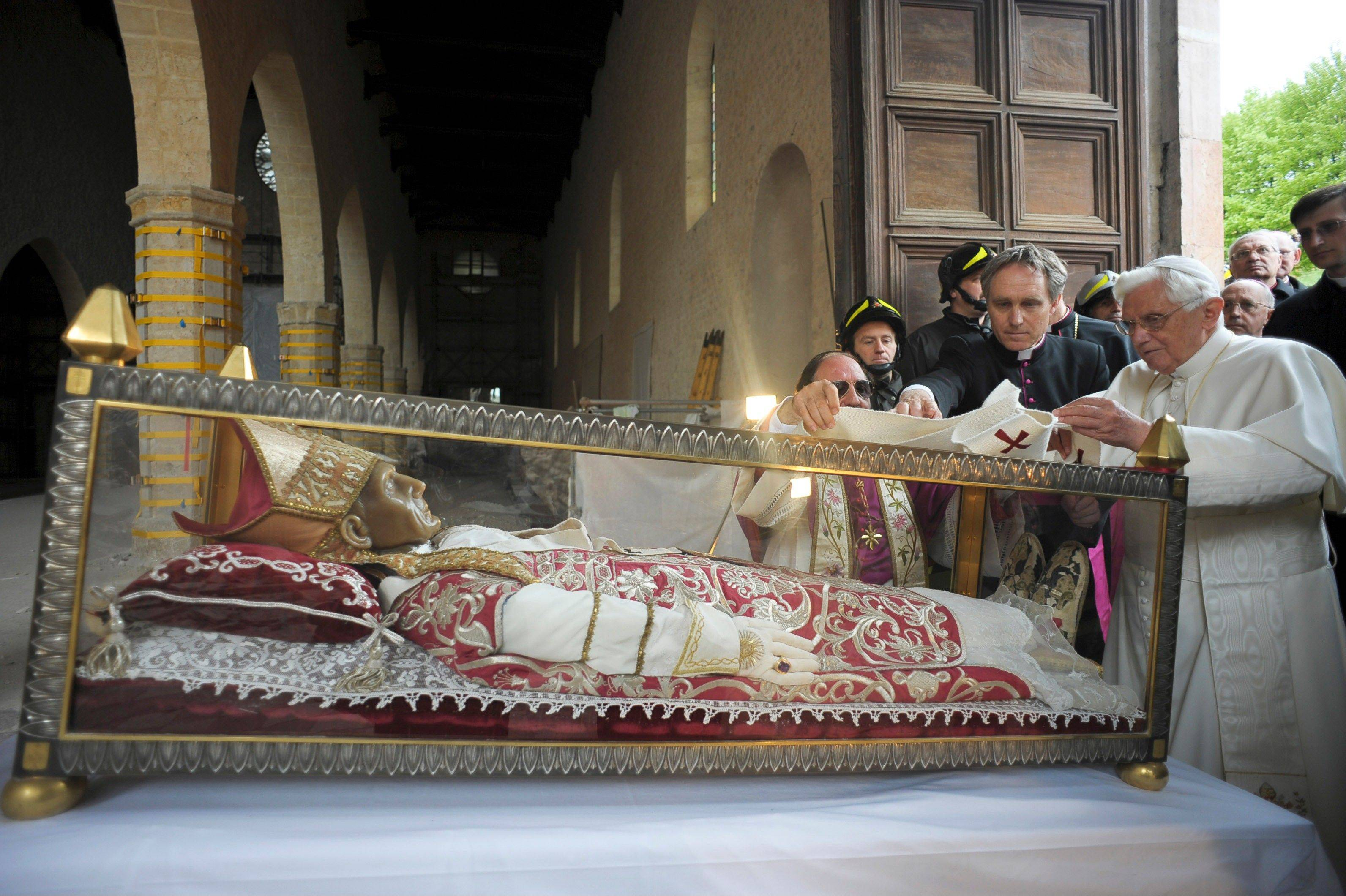 Pope Benedict XVI stands by the salvaged remains of Pope Celestine V in the 13th-century Santa Maria di Collemaggio Basilica, the symbol of the city of L'Aquila.