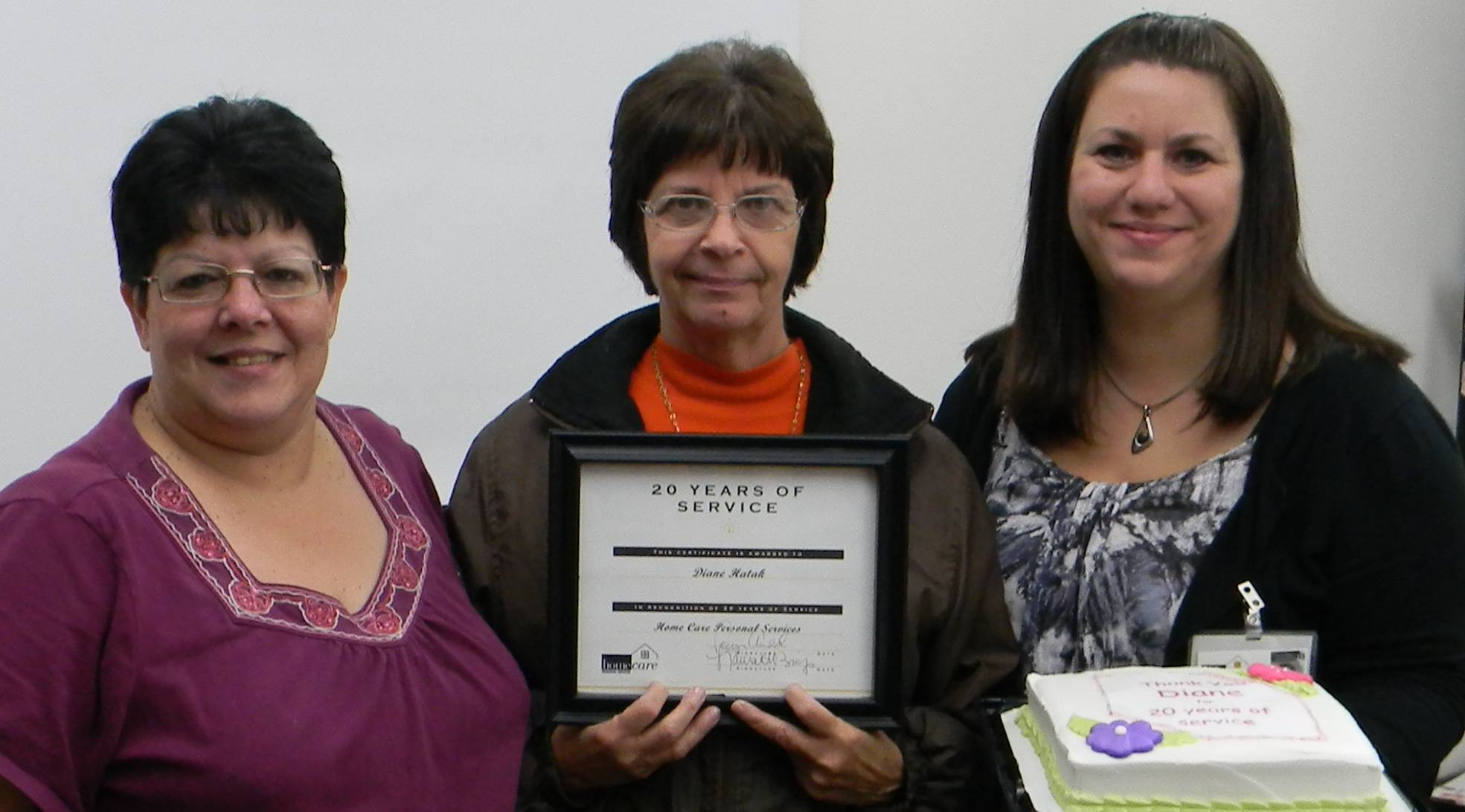 Cheryl Battista, Scheduling Supervisor, and Heather Caldwell, Scheduling Supervisor, present Diane Hatak with a plaque commending her 20 years of service to Home Care Personal Services, Inc.