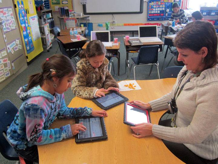Alexa Paniagua (left) and Emily Perez work with their teacher, Angel O'Rourke, during Digital Learning Day.