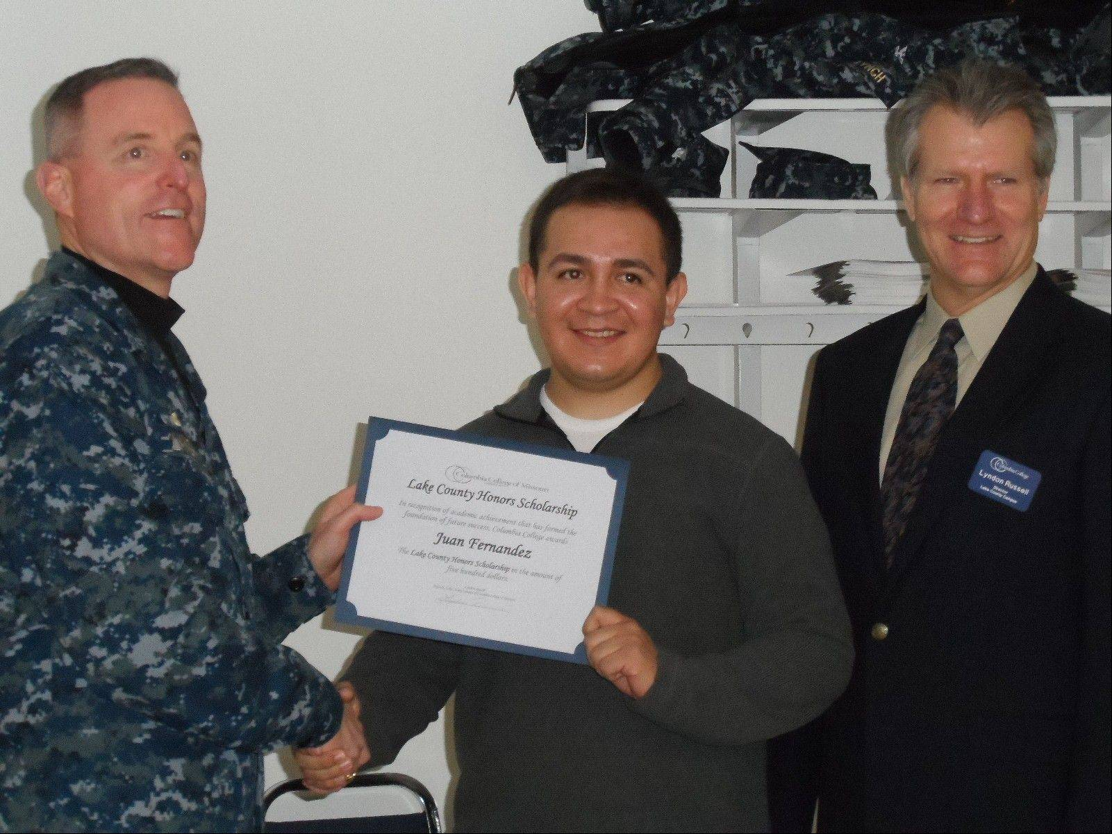 Petty Officer 2nd Class Juan Fernandez, center, receives an honors scholarship from Navy Captain Lynch, far left, at Naval Station Great Lakes during a classroom dedication by Columbia College, Columbia, Mo. Campus Director Lyndon Russell is at right.