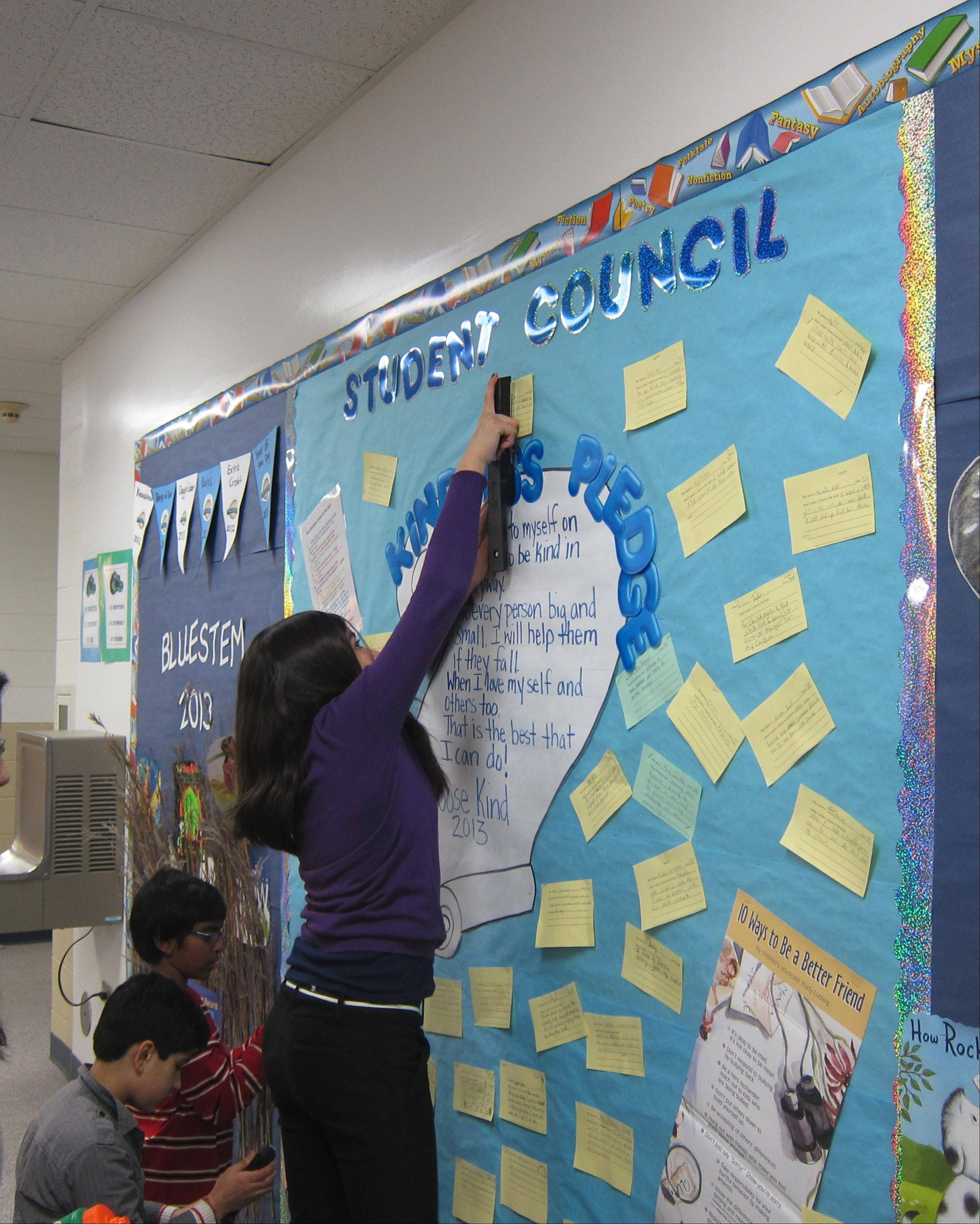 "Vansh Sikka, from left, Akhil Avasarala and Aracely Cuahuizo put up the notes that describe what Gombert Elementary School students will do as part of the Choose Kind campaign started by Naperville READS 2013 children's author R.J. Palacio, who wrote ""Wonder."""