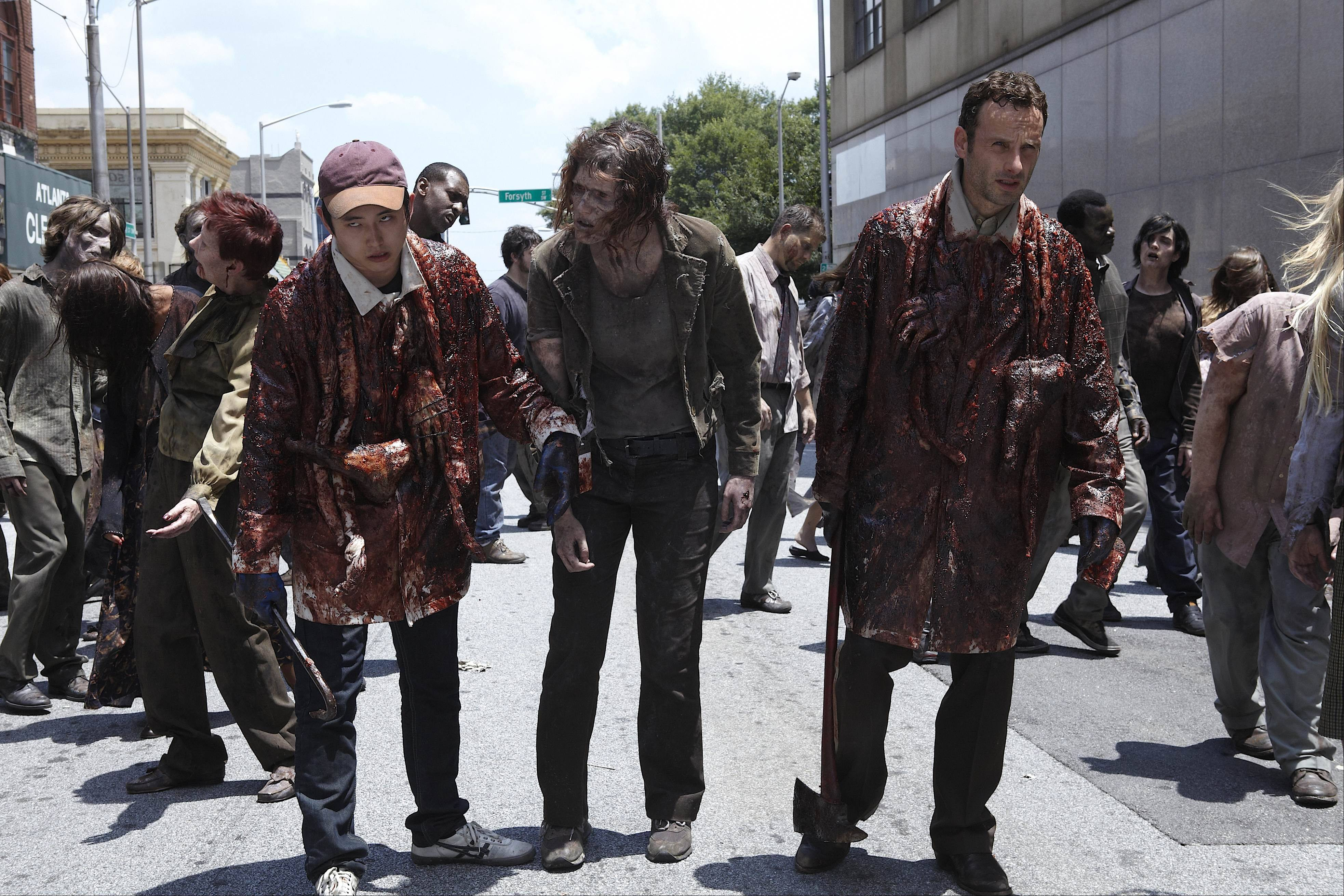"In this publicity image released by AMC, Steven Yeun, left, and Andrew Lincoln, right, try to blend in with the zombie population in a scene from ""The Walking Dead."" A Montana television station's regular programming was interrupted by news of a zombie apocalypse.The Montana Television Network says hackers broke into the Emergency Alert System of Great Falls affiliate KRTV and its CW station Monday."
