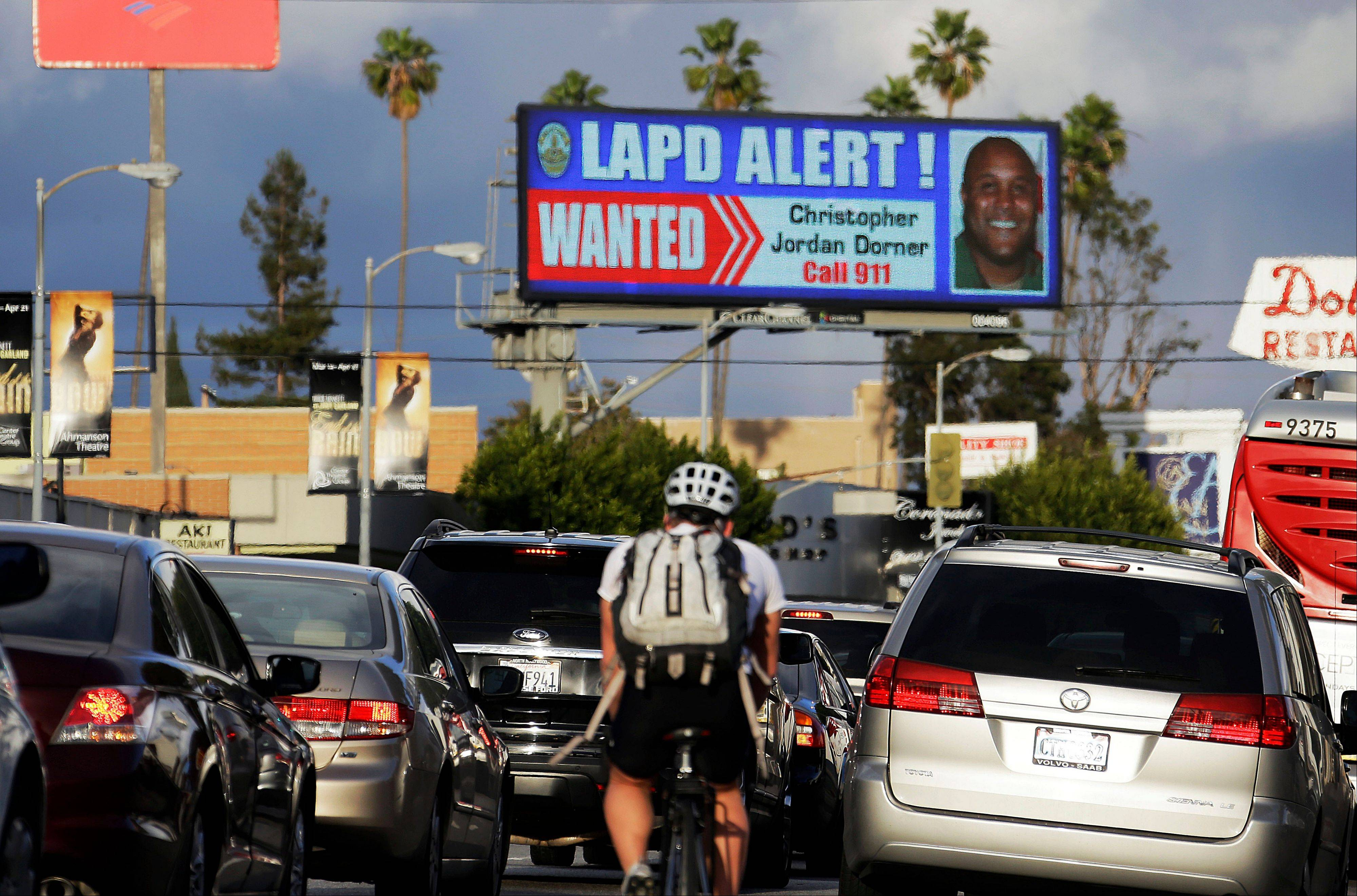 "Commuters on Santa Monica Boulevard on the Westside of Los Angeles see a digital billboard displaying a large ""wanted"" poster for former Los Angeles police Officer Christopher Dorner. Dorner is suspected in a spree of violence as part of a vendetta against law enforcement after being fired by the department. Dorner's alleged killing spree hasn't just terrorized a large section of the country — it has captured people's imagination and attention."