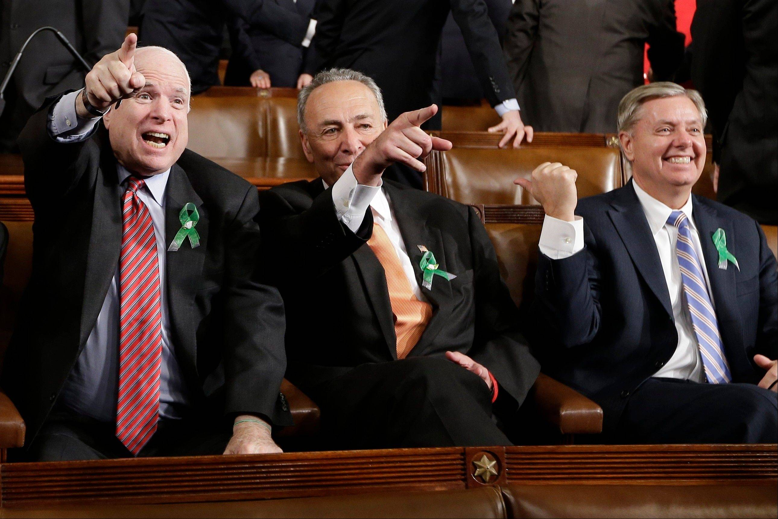From left, Sen. John McCain, a Republican, Sen. Charles Schumer, a Democrat, and Sen. Lindsey Graham, a Republican, wear green ribbons on their lapels as they wait for President Barack Obama's State of the Union address Tuesday. The green ribbons that dotted the lapels of Democrats and Republicans were in honor of the 26 students and educators killed at a Connecticut elementary school in December.