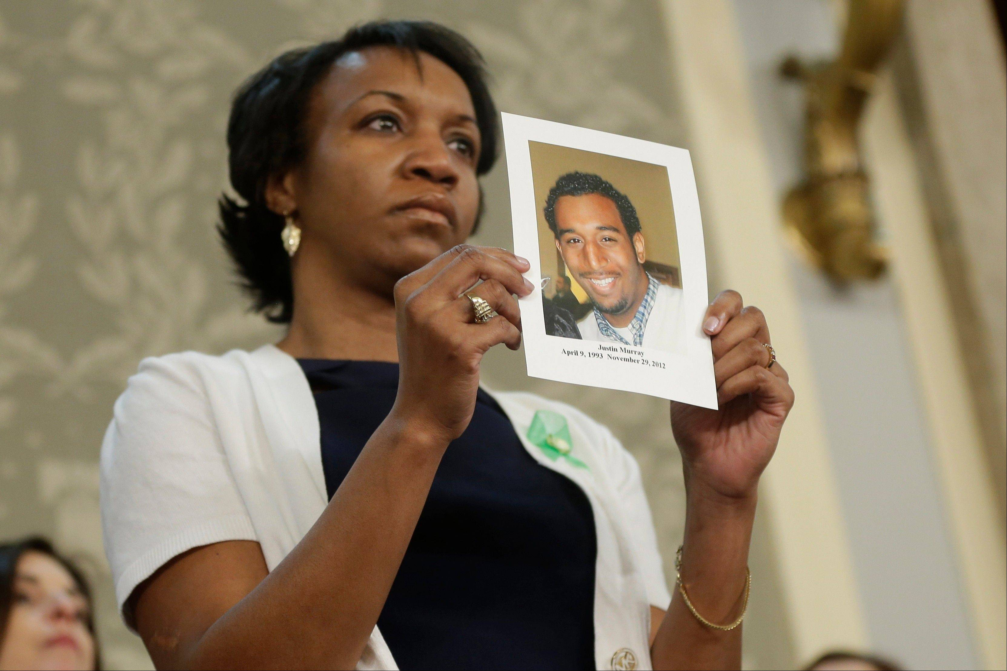 Carolyn Murray holds a photo of her slain son Justin during President Barack Obama' State of the Union address during a joint session of Congress on Capitol Hill in Washington Tuesday.