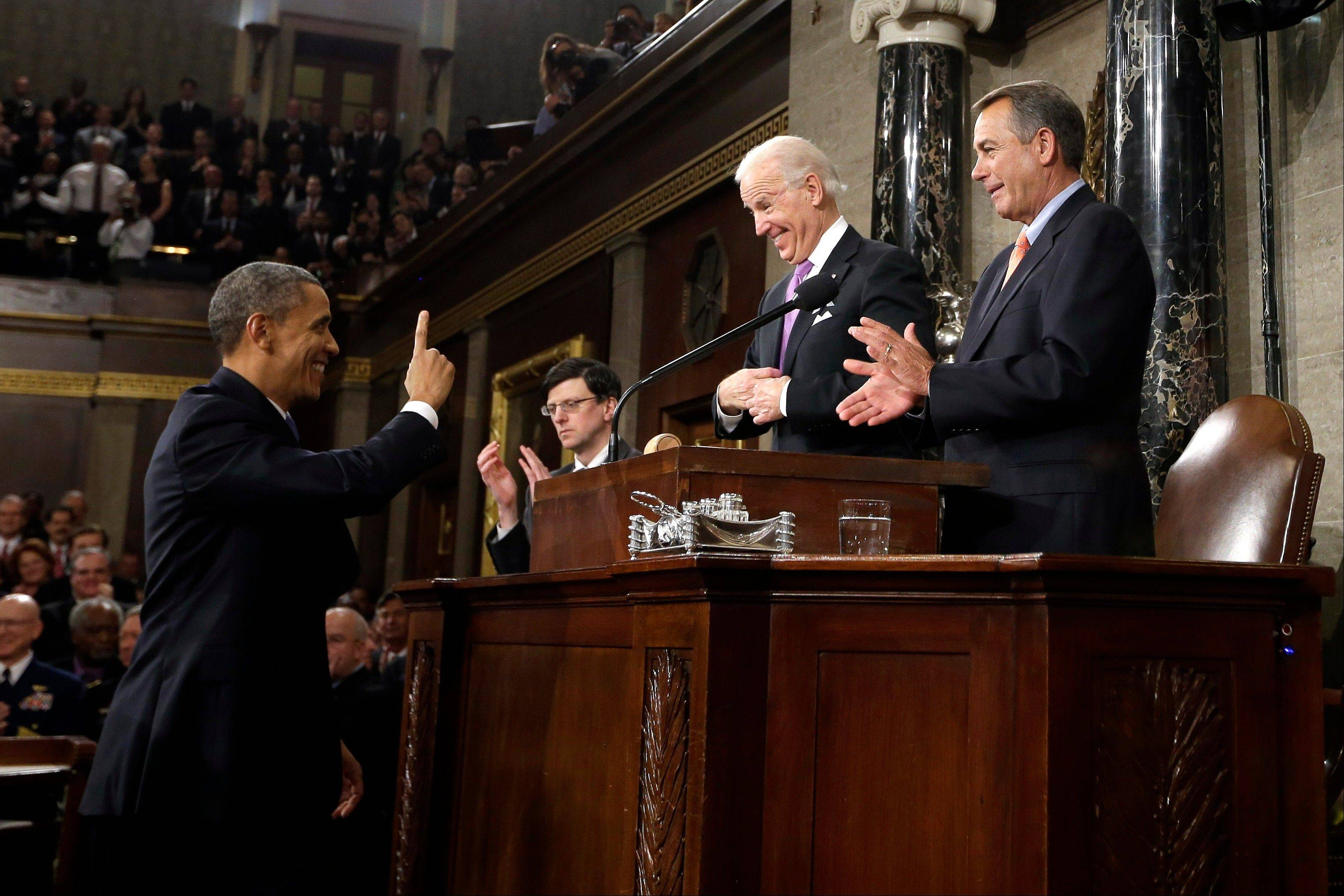 President Barack Obama gestures toward Vice President Joe Biden and House Speaker John Boehner of Ohio before giving his State of the Union address during a