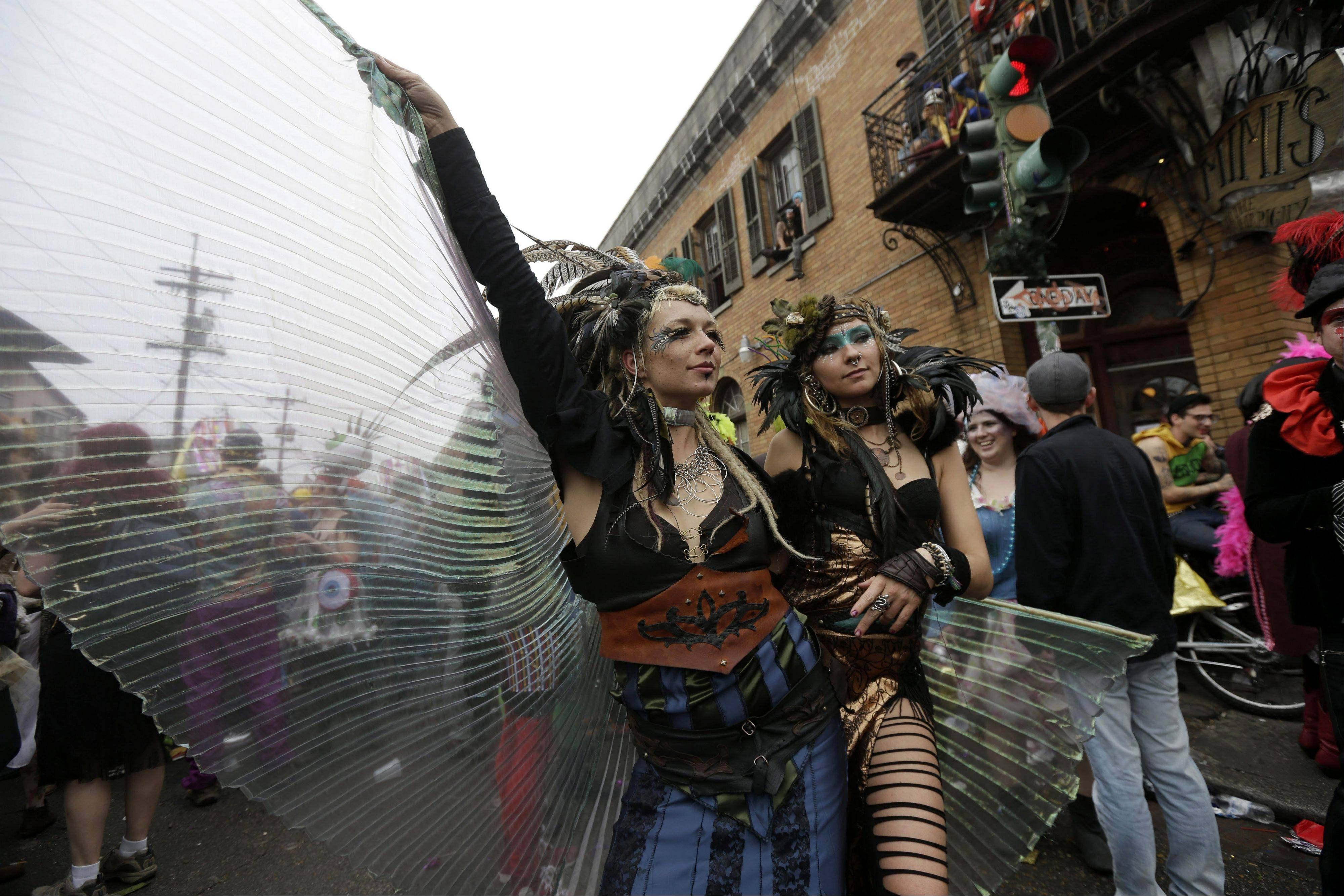 Revelers show off their costumes as they march through the Bywater section of New Orleans during the Society of Saint Anne walking parade during Mardi Gras day Tuesday.
